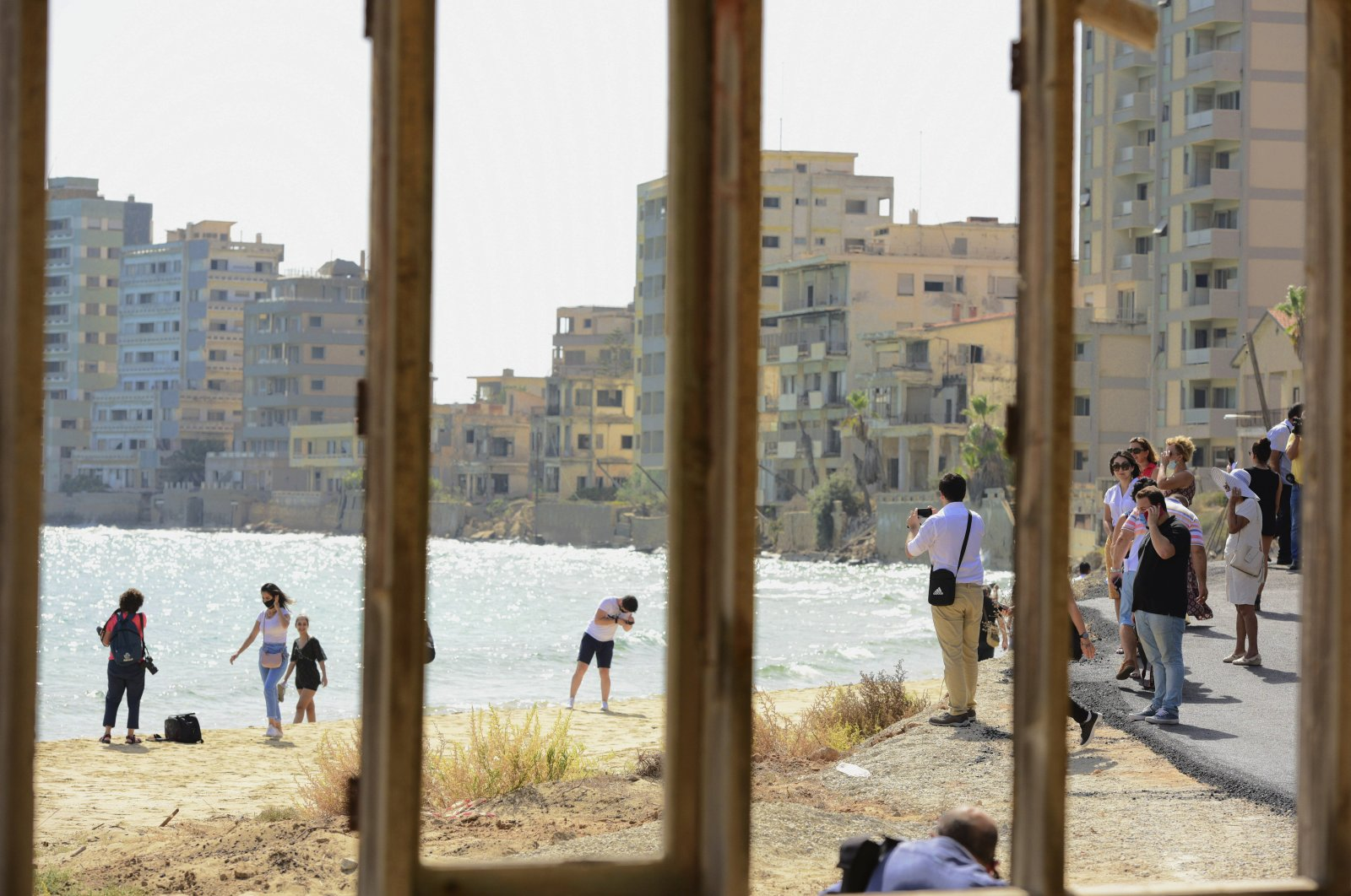Journalists and the public are seen through a window frame at the beach lined with abandoned hotels, after the reopening of Varosha, in the fenced-off area of Gazimağosa (Famagusta), TRNC, Oct. 8, 2020. (AP Photo)