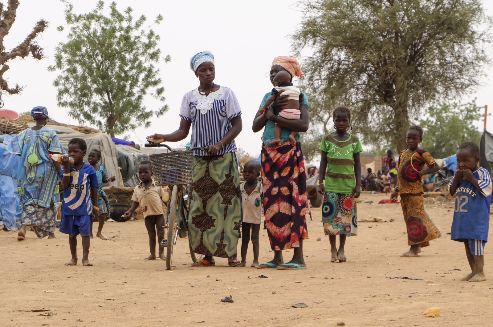 Women and children walk through a makeshift site for displaced people in Kongoussi, Burkina Faso, June 4, 2020. (AP Photo)