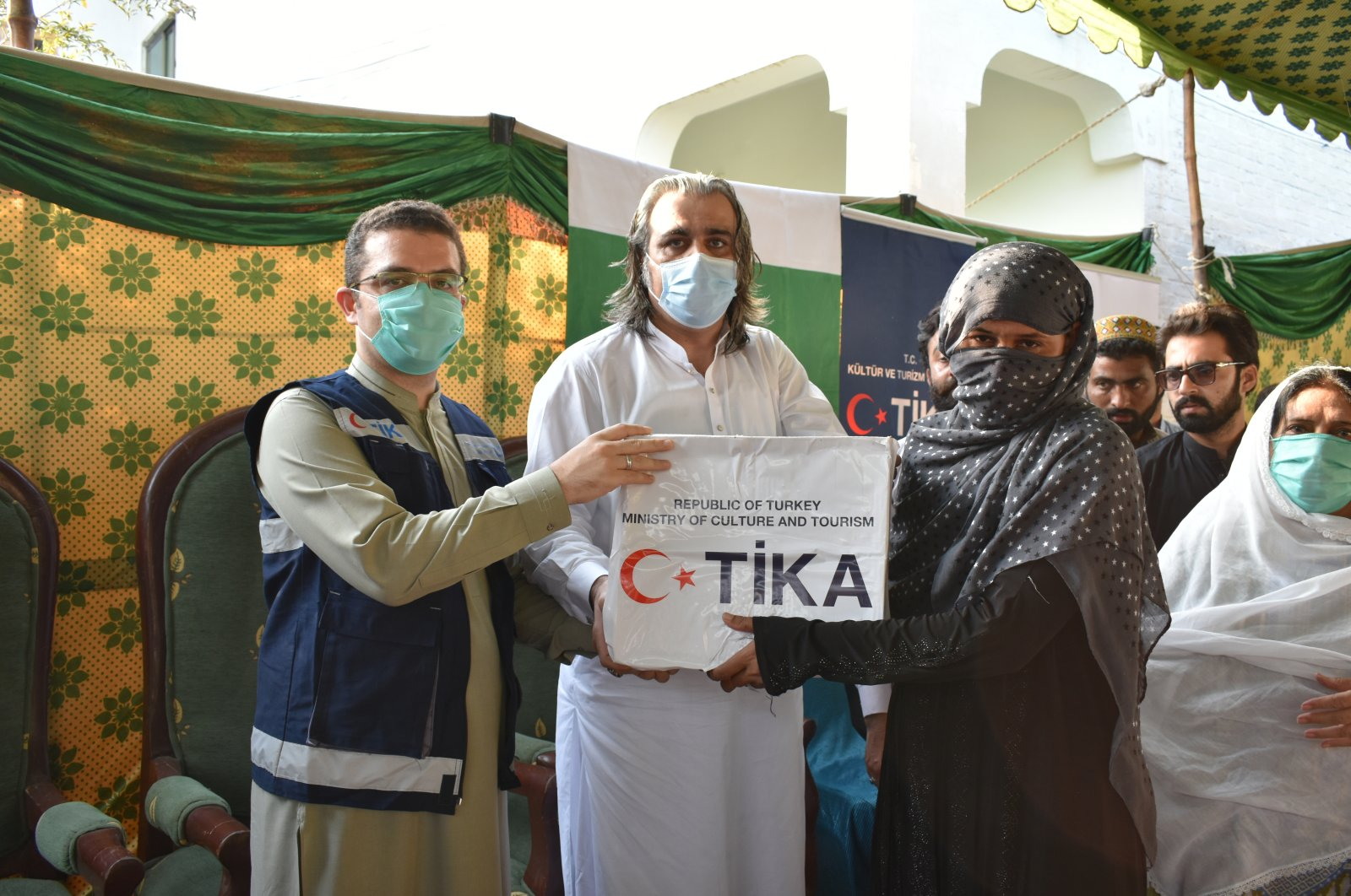 TİKA official Gökhan Umut (L) and Ali Amin Khan Gandapur, Federal Minister for Kashmir Affairs and Gilgit-Baltistan (C), deliver aid to families, Dera Ismail Khan, Pakistan, Oct. 20, 2020. (AA Photo)