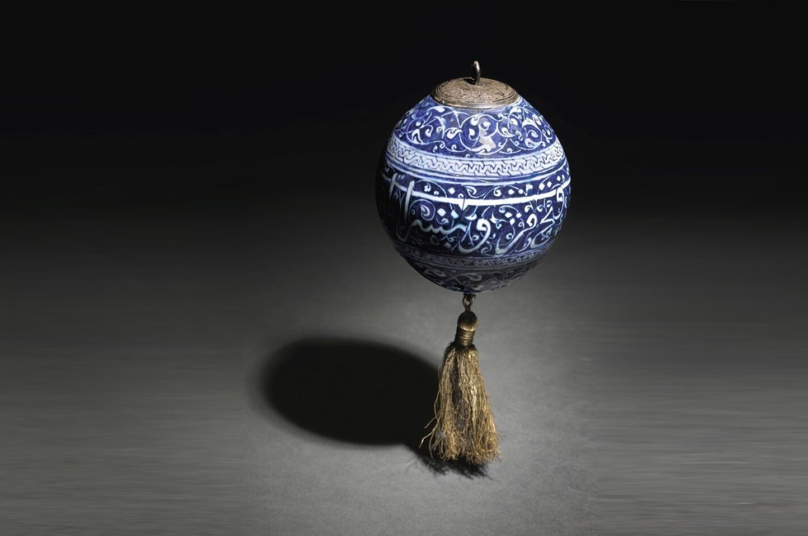 The body of the hanging ornament is decorated in underglaze cobalt blue with a calligraphic band against leafy scrolls and topped with a metal mount, while the bottom features a hoop and tassel. ( İHA PHOTO)