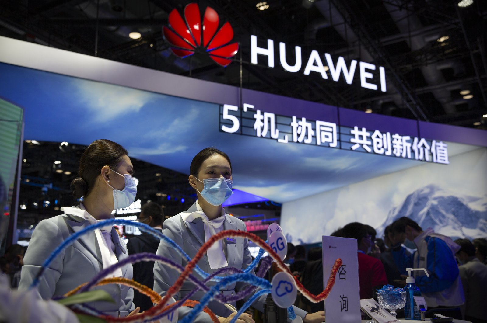 Staff members wearing face masks to protect against the coronavirus stand at a booth from Chinese technology firm Huawei at the PT Expo in Beijing, Oct. 14, 2020. (AP Photo)