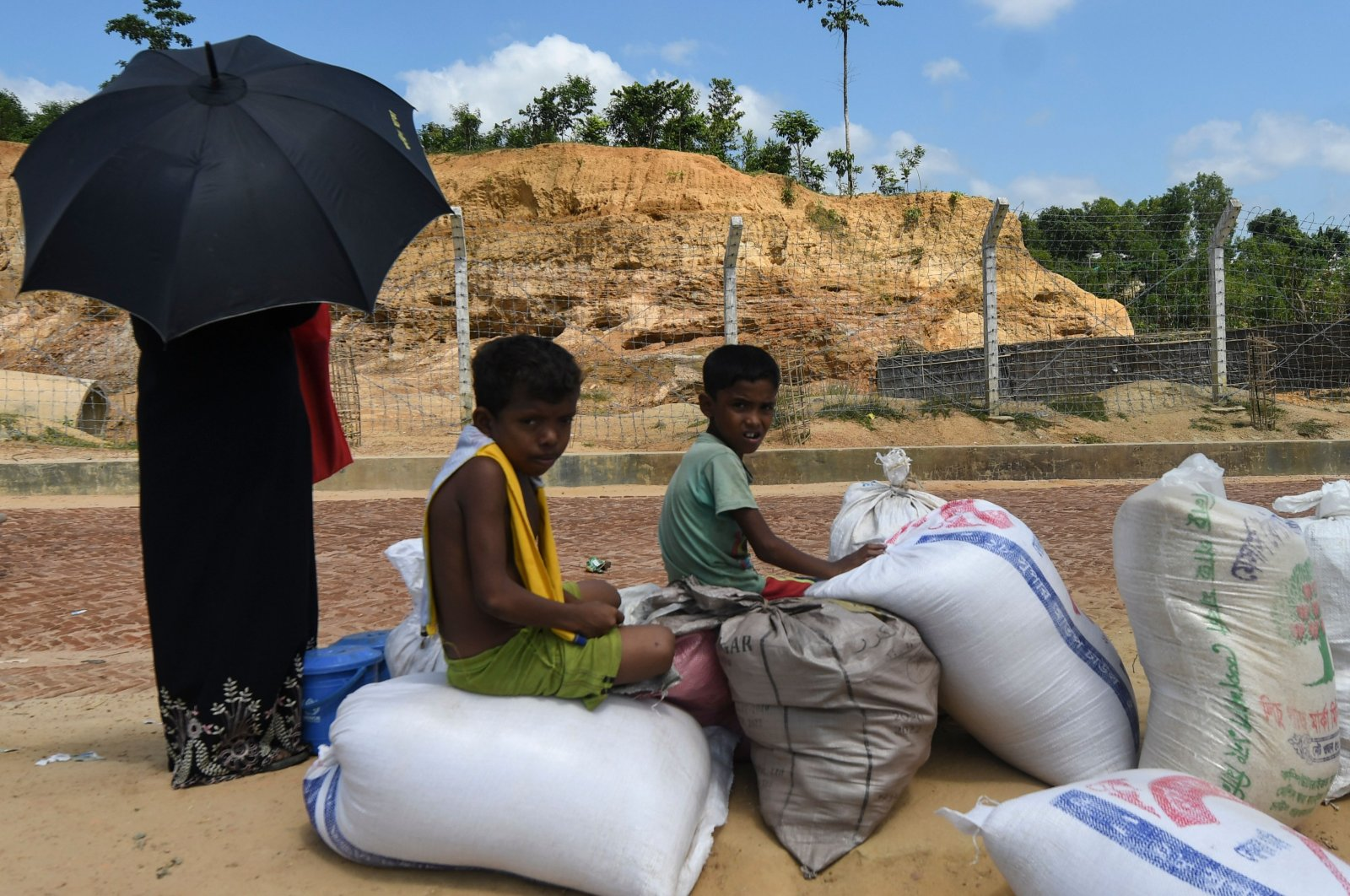 Rohingya refugee children sit on relief supplies at Kutupalong refugee camp in Ukhia, Bangladesh, Oct. 15, 2020. (AFP Photo)