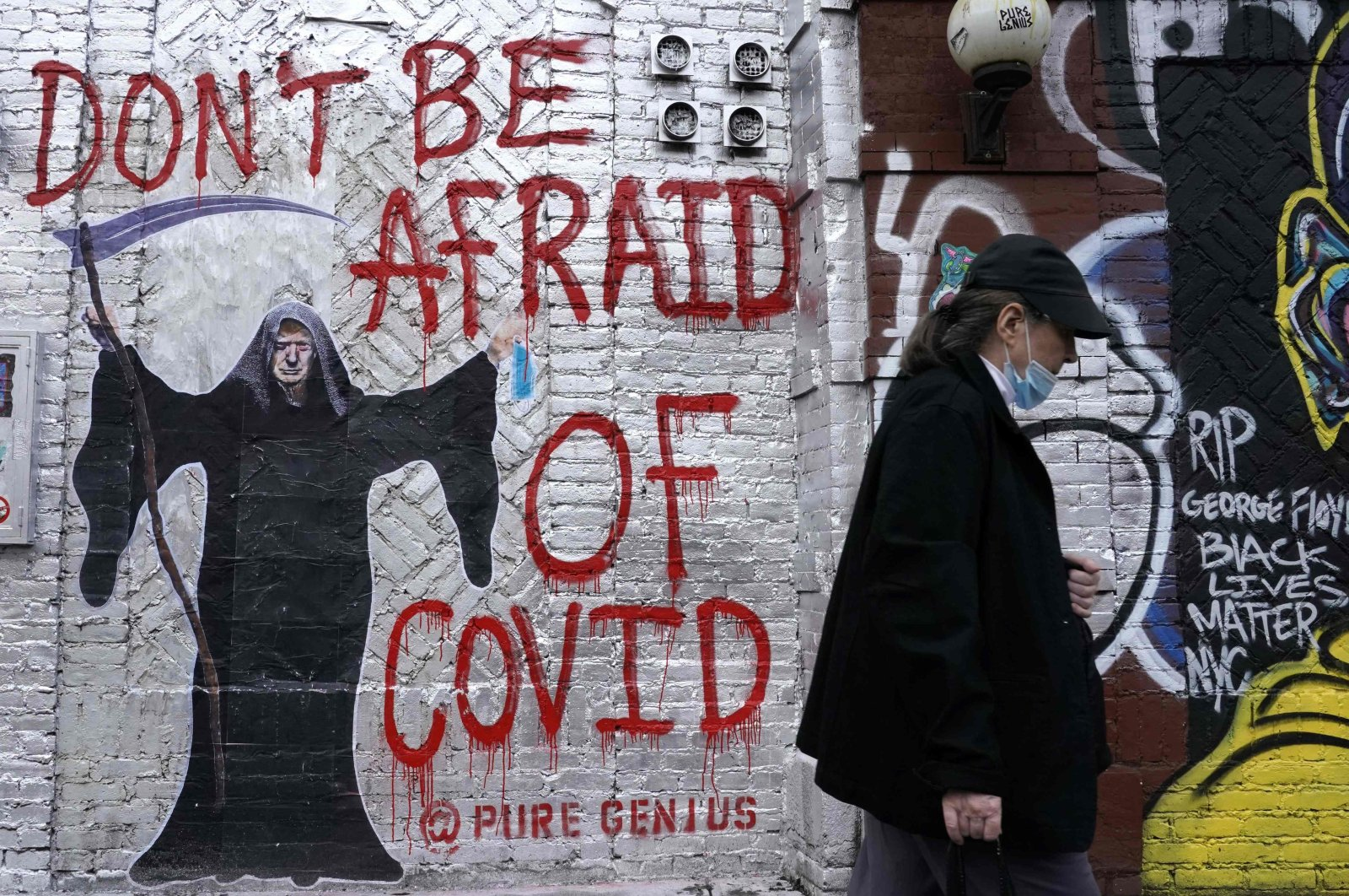 """A person walks past a mural by an artist who goes by """"Pure Genius"""" depicting U.S. President Donald Trump as the Grim Reaper on a wall on Houston Street, New York City, Oct. 20, 2020. (AFP Photo)"""