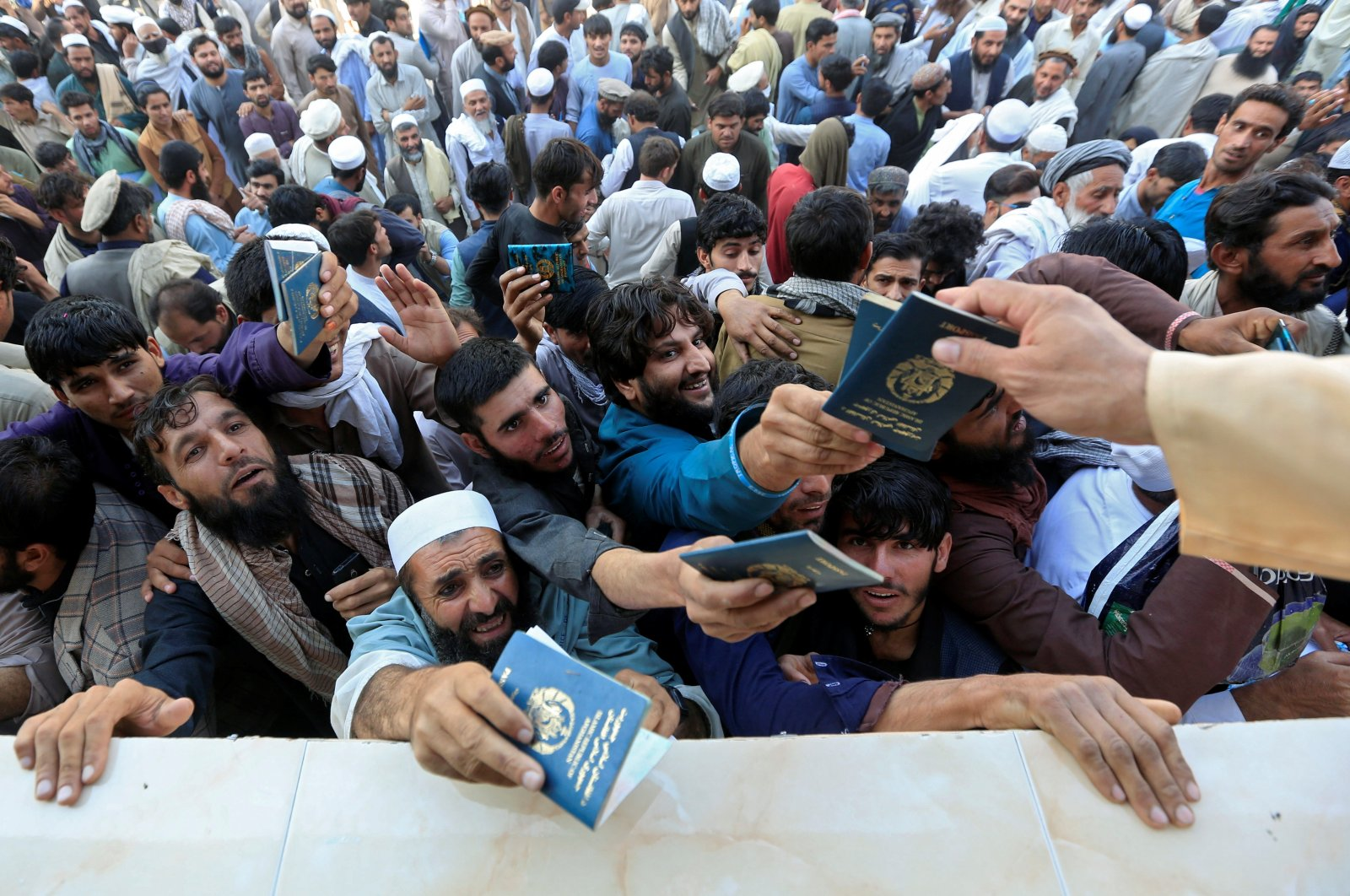 Afghan men wait to collect tokens needed to apply for the Pakistan visa, in Jalalabad, Afghanistan, Oct. 21, 2020. (Reuters Photo)