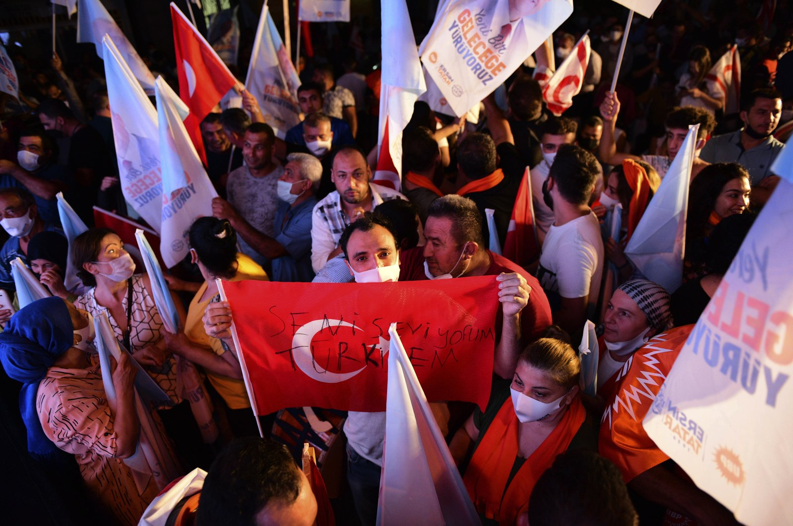 A supporter of newly elected Turkish Cypriot leader Ersin Tatar holds a Turkish flag and celebrates with others in the capital Lefkoşa (Nicosia), Oct. 18, 2020. (AP Photo)