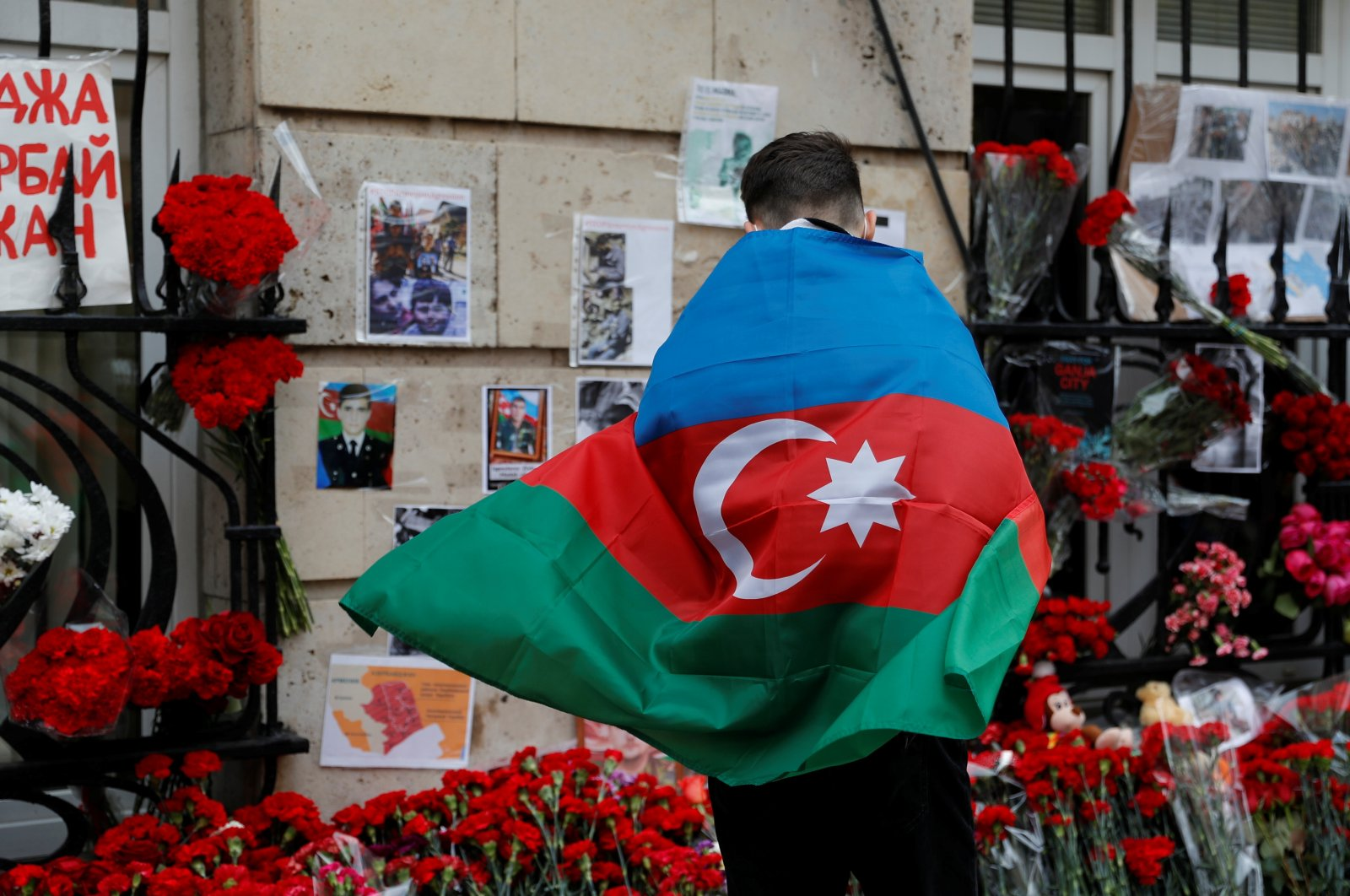 A man holding the national flag of Azerbaijan stands next to a makeshift memorial for people killed in the country during the military conflict over the occupied region of Nagorno-Karabakh, outside the Embassy of Azerbaijan in Moscow, Oct. 19, 2020. (Reuters Photo)
