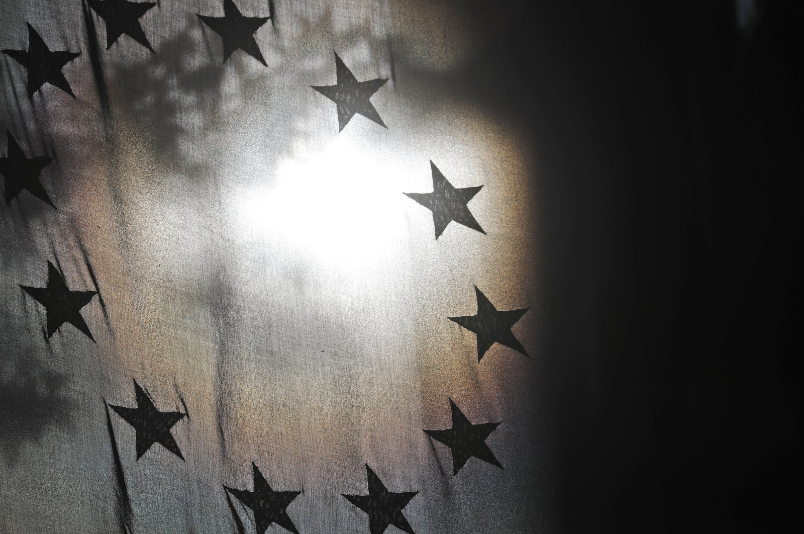 The stars of the EU flag are seen against the sun at the Europa House in London, Oct. 19, 2020. (AP Photo)