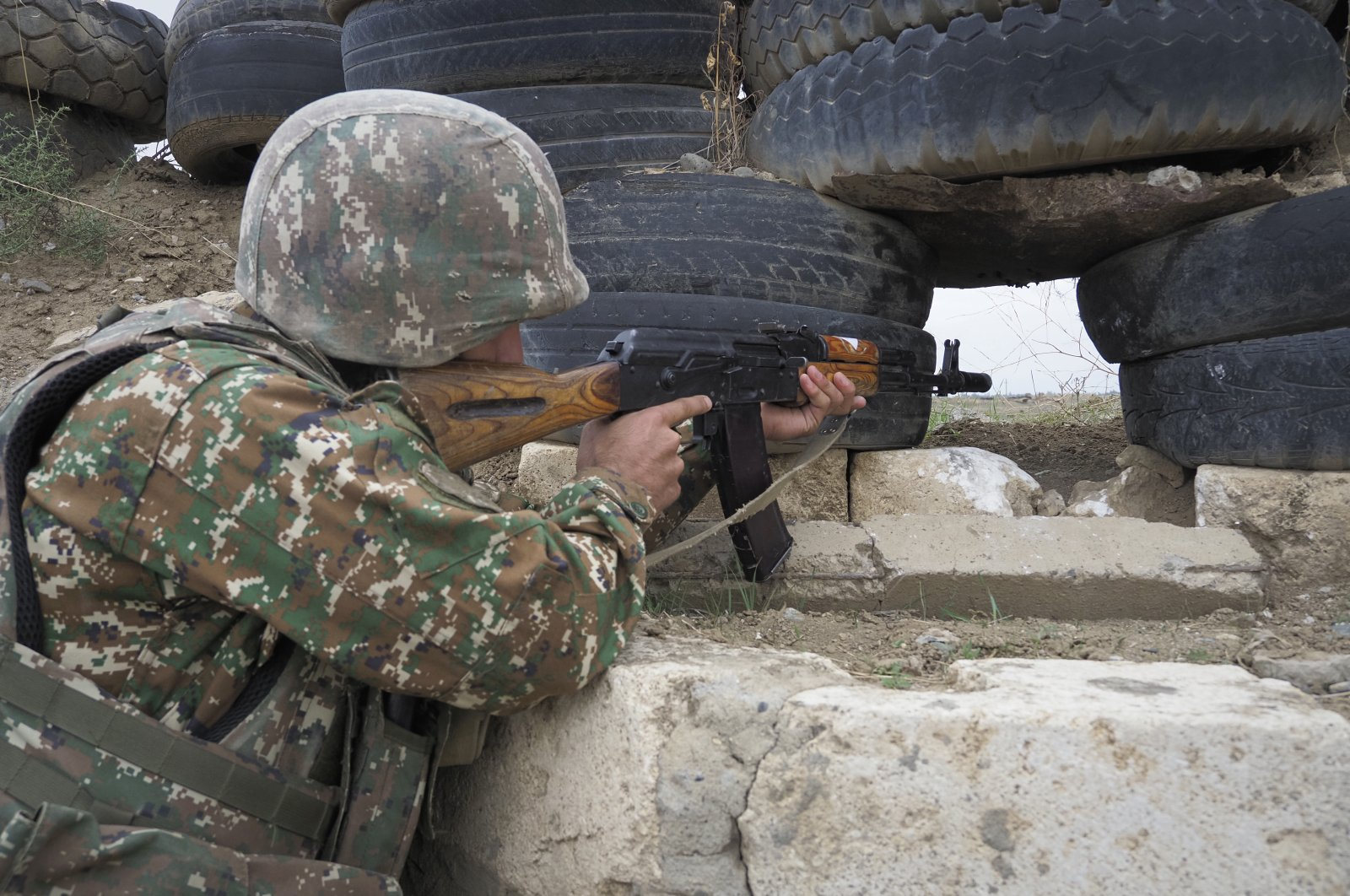An Armenian soldier holds a Kalashnikov machine gun as he looks toward Azerbaijan's positions from a dugout at a fighting position on the front line, during a military conflict against Azerbaijan, Oct. 21, 2020. (AP Photo)