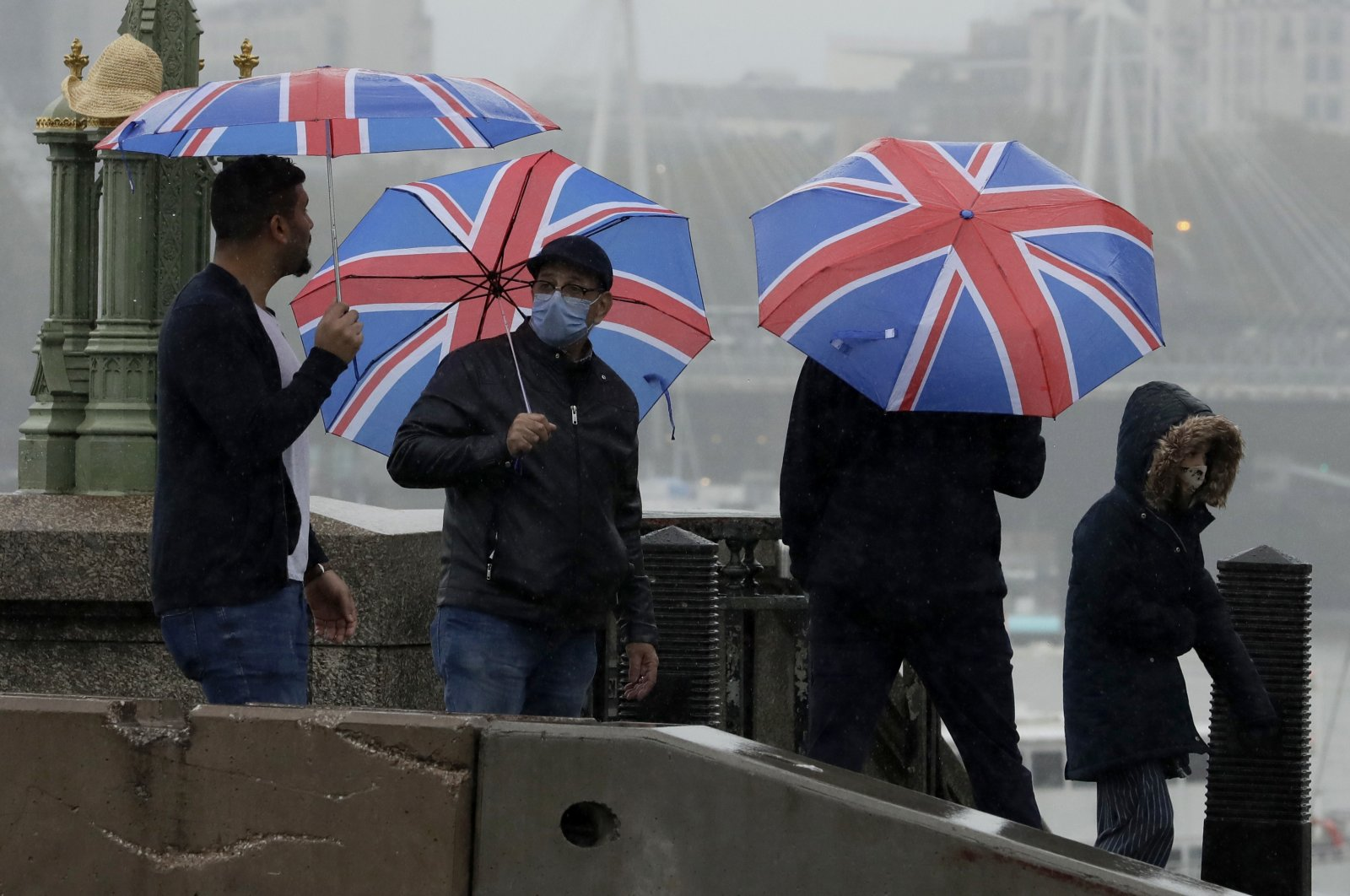 A man wearing a face mask to try to curb the spread of coronavirus holds a British union flag umbrella on Westminster Bridge in central London, Wednesday, Oct. 21, 2020. (AP Photo)