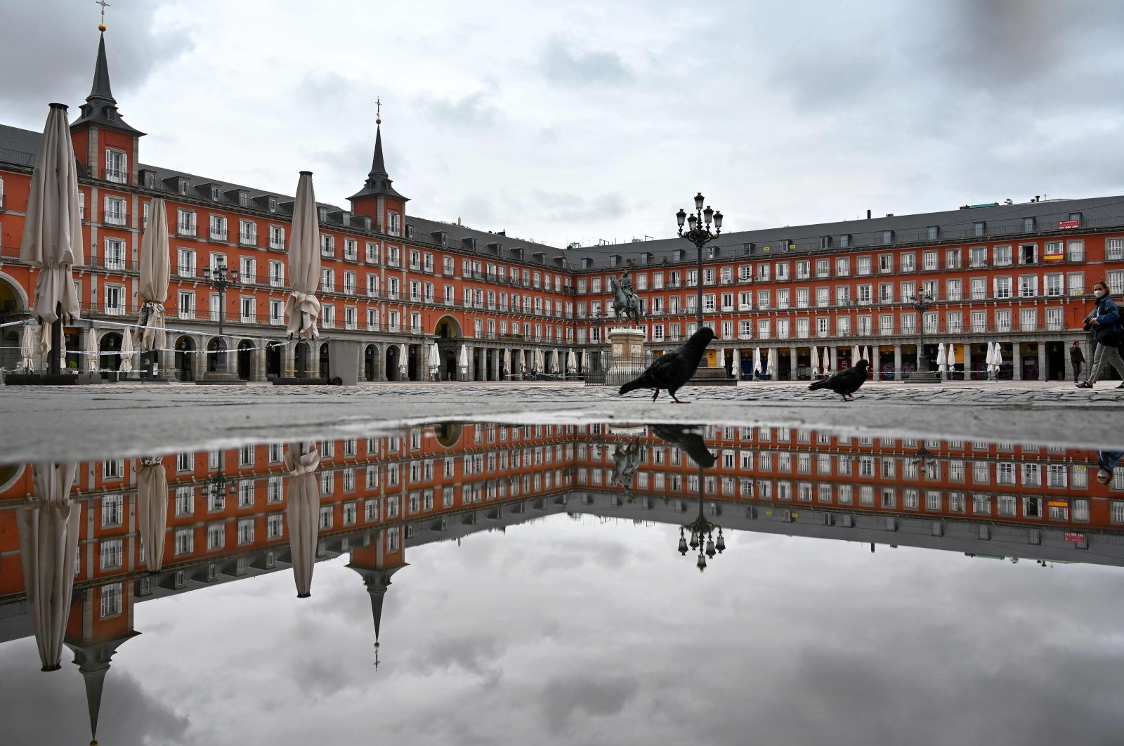 In this April 21, 2020 file photo, a lone person crosses the deserted Plaza Mayor square in Madrid amid a national lockdown to fight the spread of the coronavirus. (AFP Photo)