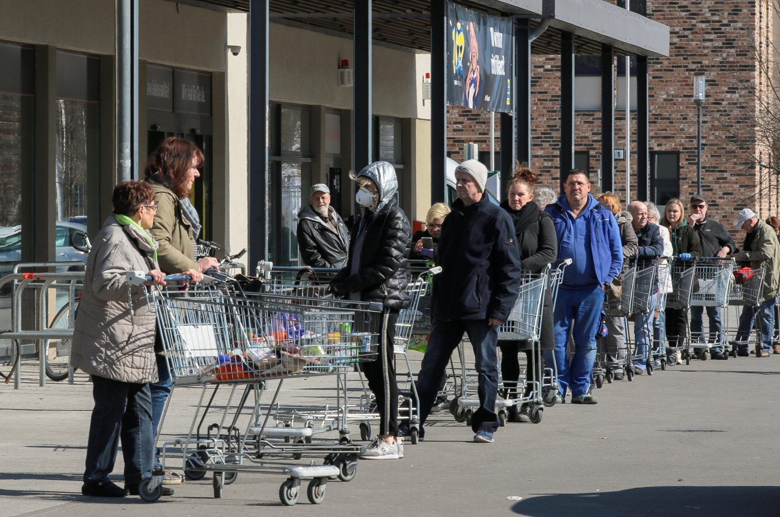 Shoppers leave as others wait in a queue to enter a supermarket in Schulzendorf near Berlin, during the coronavirus outbreak, Germany, March 25, 2020. (Reuters Photo)