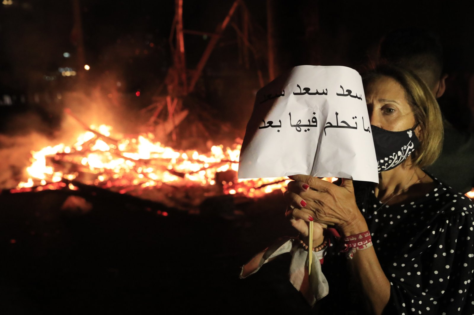 "A protester holds an Arabic placard that reads: ""Saad don't dream on it any more,"" Beirut, Oct. 21, 2020. (AP Photo)"