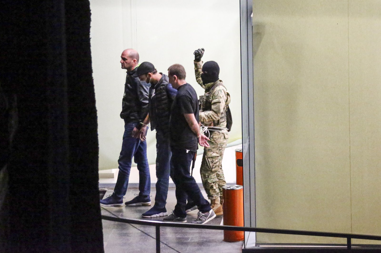 A gunman with a weapon in his hand, escorts three police officers, who surrendered themselves as hostages, out of the bank building in the town of Zugdidi in western Georgia, Oct. 21, 2020. (AP Photo)
