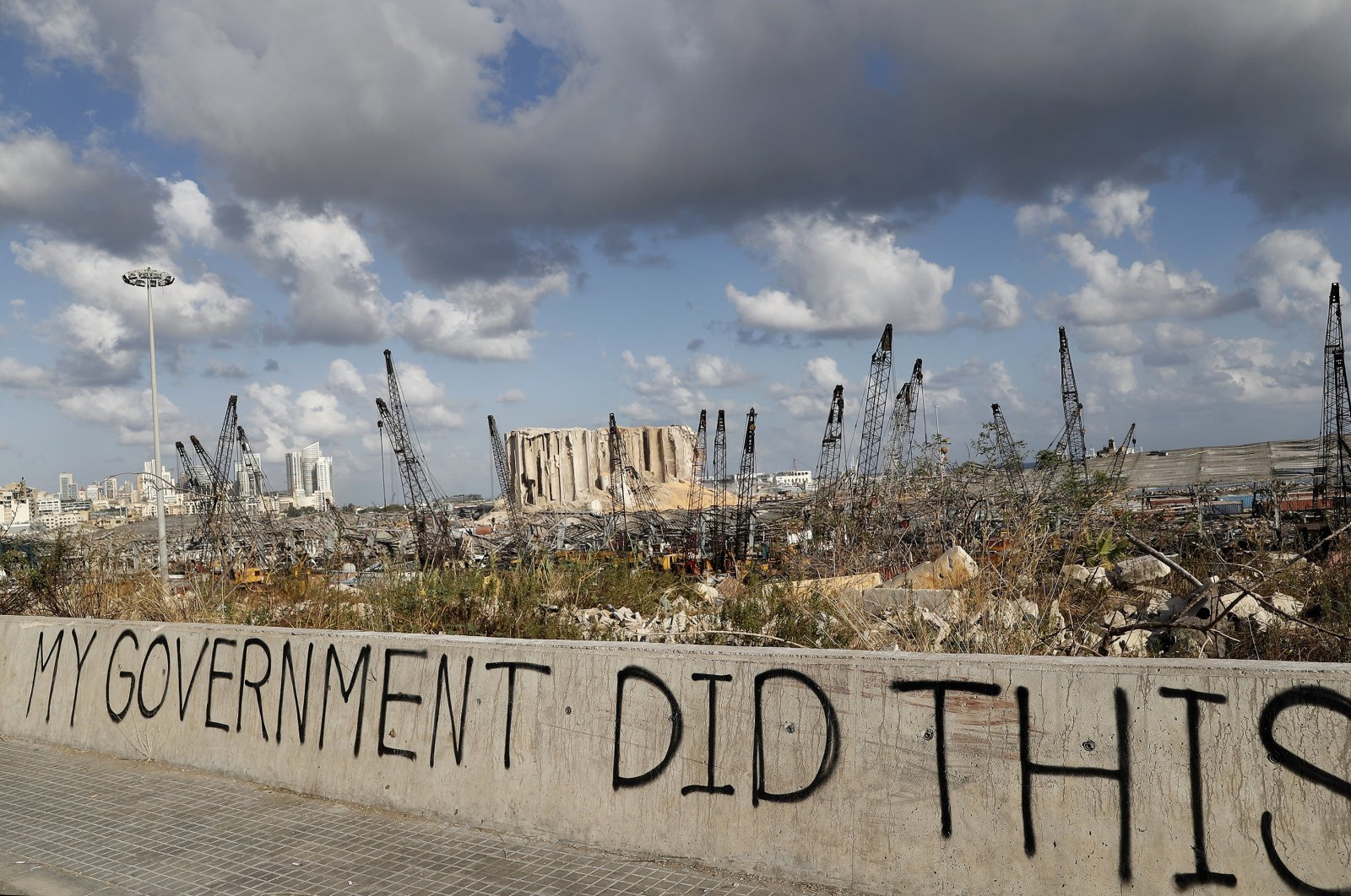A political graffiti is visible in front of the scene of the port, Beirut, Aug. 9, 2020. (AP Photo)