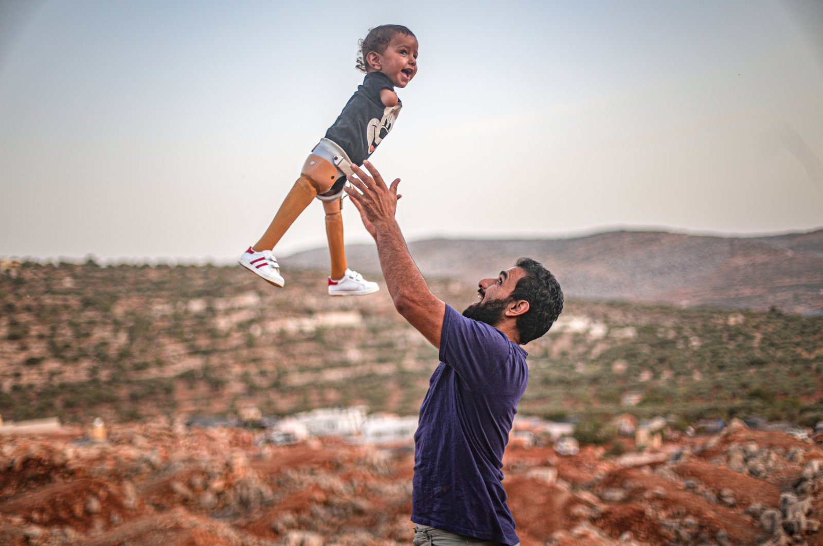 Father Khaled bounces his son Muhammad, in Idlib, Syria, Oct. 22, 2020. (AA Photo)