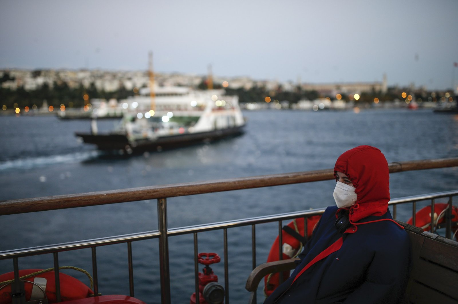 A woman, wearing a protective mask to help prevent the spread of the coronavirus, takes a boat trip over the Bosporus separating the Asian and the European sides of Istanbul, Turkey, Wednesday, Oct. 21, 2020. (AP Photo)