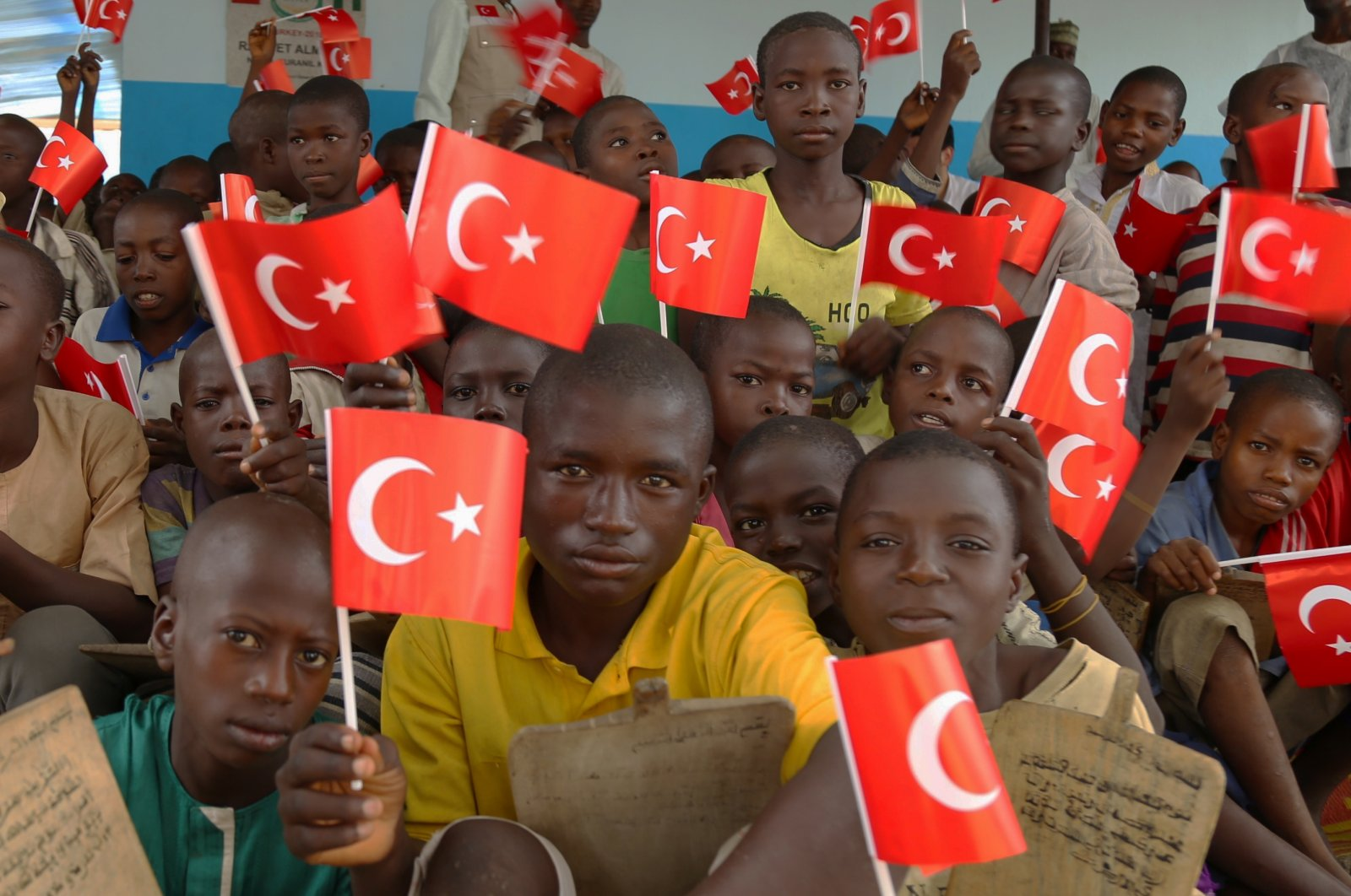 Students hold Turkish flags in a dormitory restored by donations provided by Turkish charitiesand businesspeople, in the capital Abuja, Nigeria,Oct. 4,2019. (AA Photo)