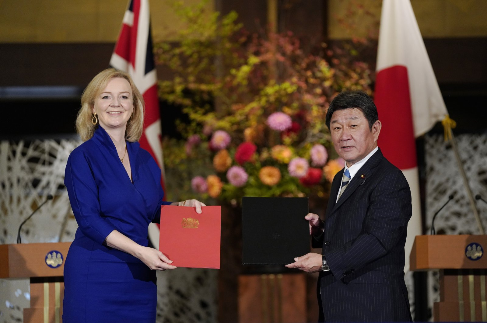 British International Trade SecretaryLiz Truss, left, and Japanese Foreign Minister Toshimitsu Motegi exchange agreement documents for economic partnership between Japan and Britain at Iikura Annex of the Foreign Ministry in Tokyo, Friday, Oct. 23, 2020. (Pool Photo via AP)