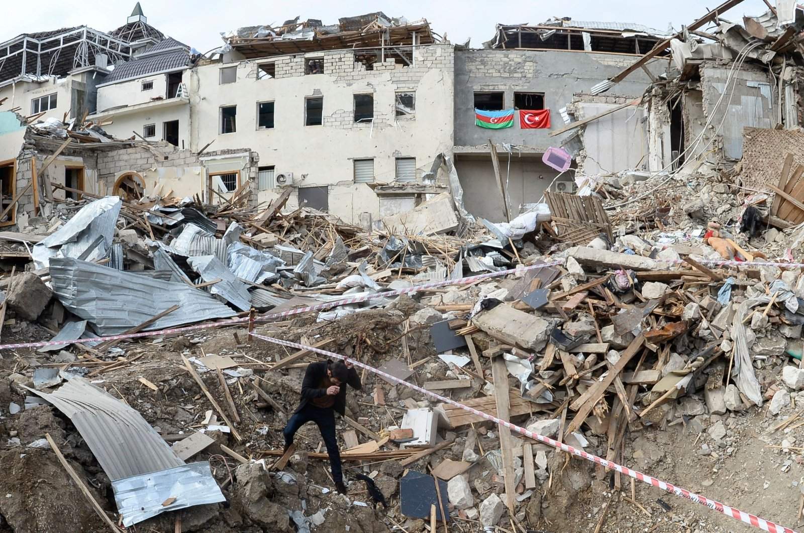 A man walks among the debris of destroyed buildings hit by Armenian shelling, in a residential area of the city of Ganja, Azerbaijan, on Oct. 22, 2020. (AFP Photo)