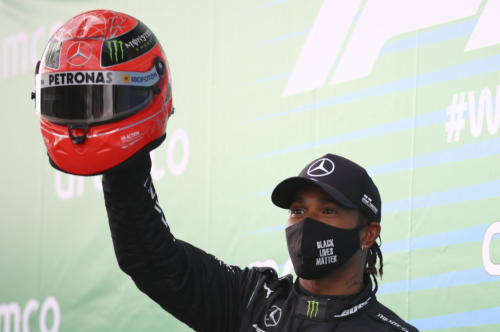 Lewis Hamilton shows a helmet of legendary driver Michael Schumacher, which was gifted to him, after he wins the Eifel Grand Prix in Nuerburg, Germany, Oct. 11, 2020. (AP Photo)