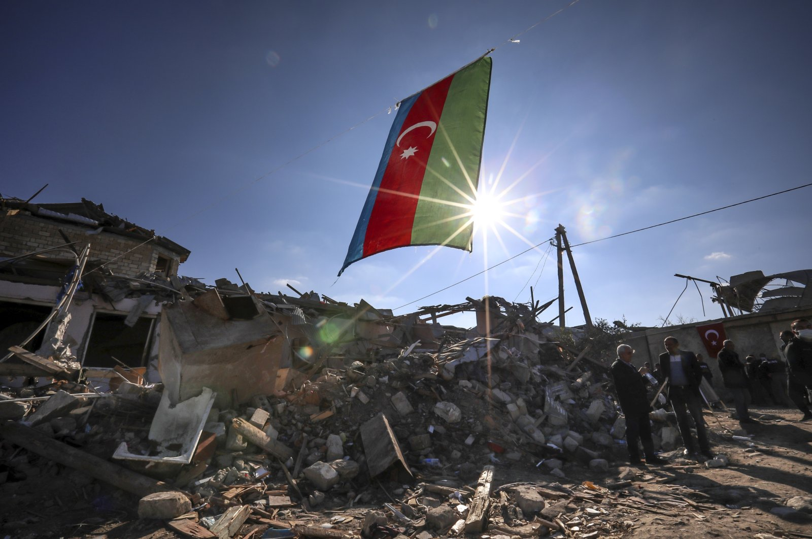 Azerbaijan's national flag flies over destroyed houses in a residential area that was hit by rocket fire overnight by Armenian forces in Ganja, Azerbaijan, Oct. 22, 2020. (AP Photo)