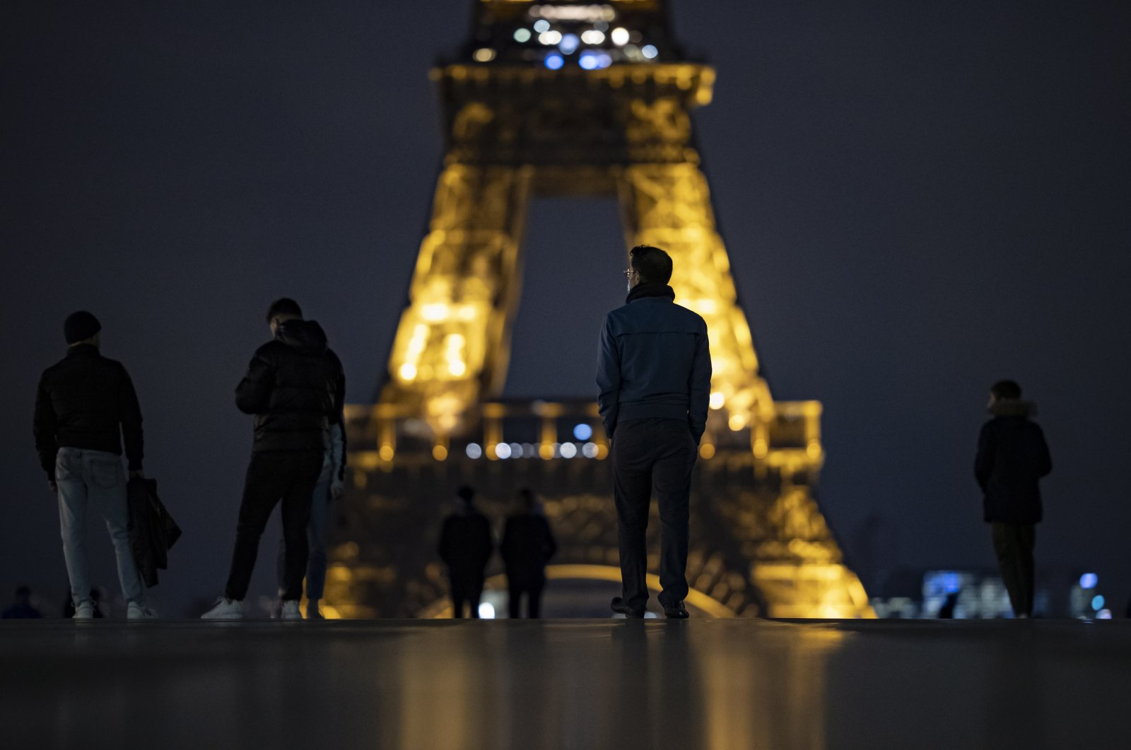 People wearing protective face masks walk near the Eiffel Tower at nightfall, just hours before a city-wide night-time curfew goes into effect in Paris, France, Oct. 16, 2020. (EPA Photo)