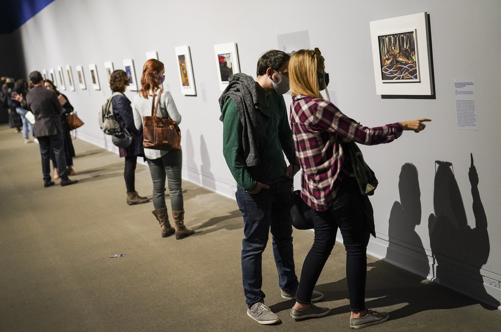 """Visitors wearing masks observe COVID-19 prevention protocols as they browse the """"Jacob Lawrence: The American Struggle"""" exhibition at the Metropolitan Museum of Art, in New York, Oct. 17, 2020. (AP Photo)"""