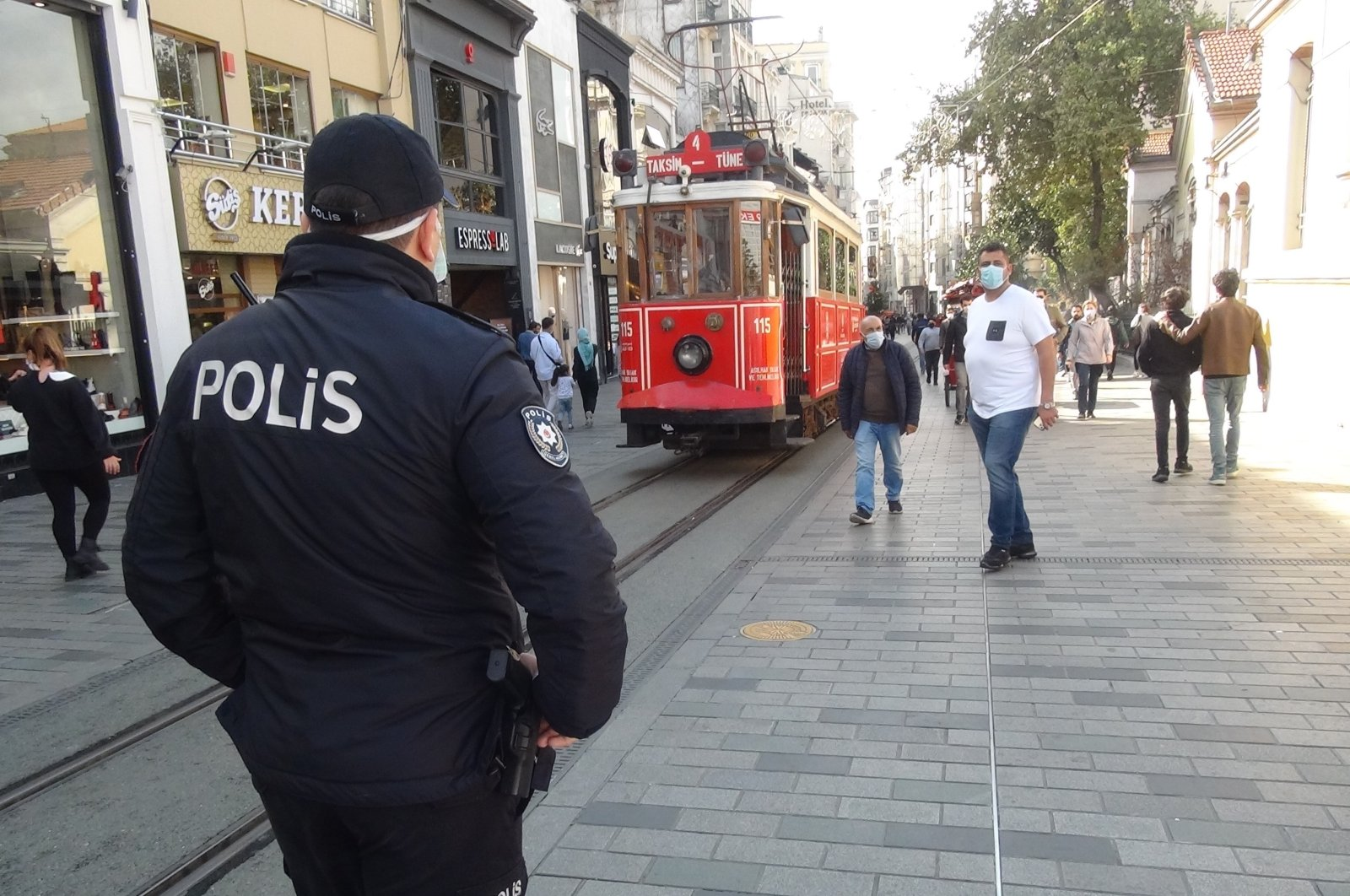 A police officer inspects people against violation of COVID-19 rules on Istiklal Avenue, in Istanbul, Turkey, Oct. 21, 2020. (İHA Photo)