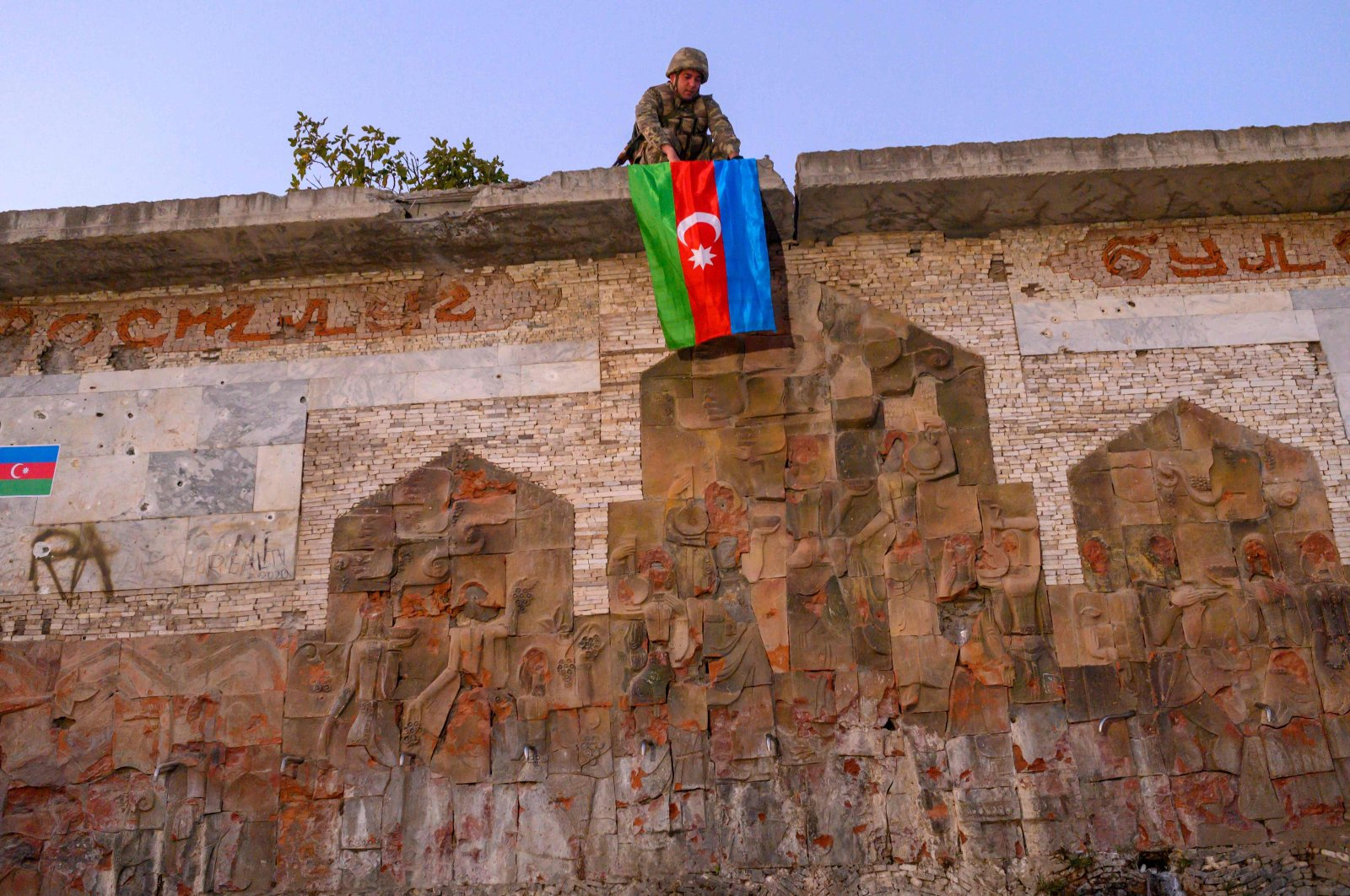 An Azerbaijani soldier hangs the flag of Azerbaijan in the city of Jabrayil, where Azerbaijani forces regained control during the clashes with Armenia over occupied Nagorno-Karabakh on Oct. 16, 2020. (AFP Photo)