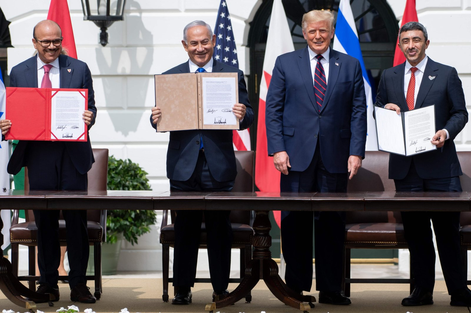 (L-R)Bahrain Foreign Minister Abdullatif al-Zayani, Israeli Prime Minister Benjamin Netanyahu, U.S. President Donald Trump and UAE Foreign Minister Abdullah bin Zayed al-Nahyan hold up documents after participating in the signing of the Abraham Accords where the countries of Bahrain and the UAE recognize Israel, at the White House in Washington, D.C., Sept. 15, 2020. (AFP Photo)