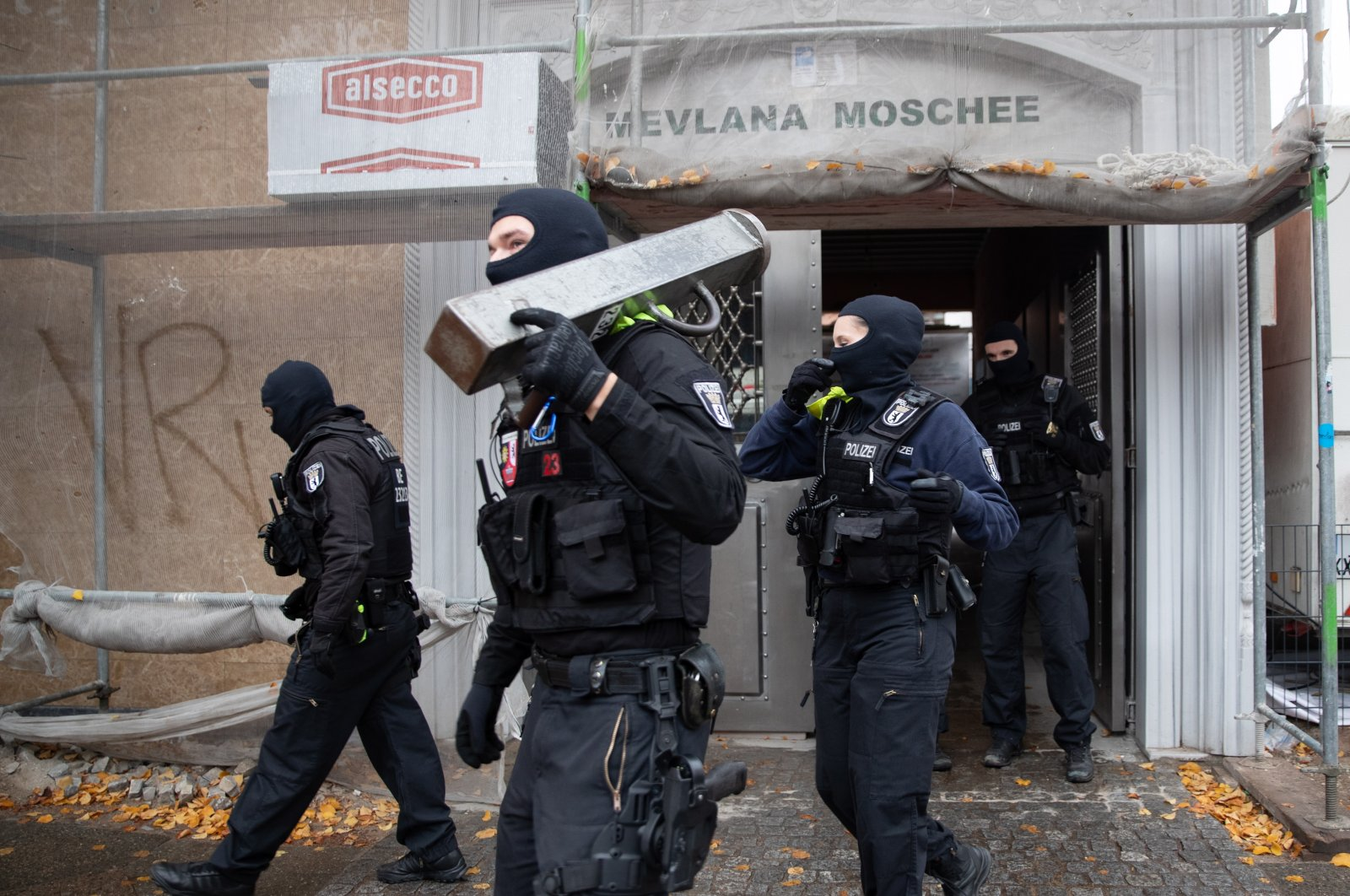 Police officers carry a metal bar to break doors in front of the entrance of Mevlana Mosque in Berlin-Kreuzberg during a police raid, in Berlin, Germany, Oct. 21, 2020. (EPA Photo)