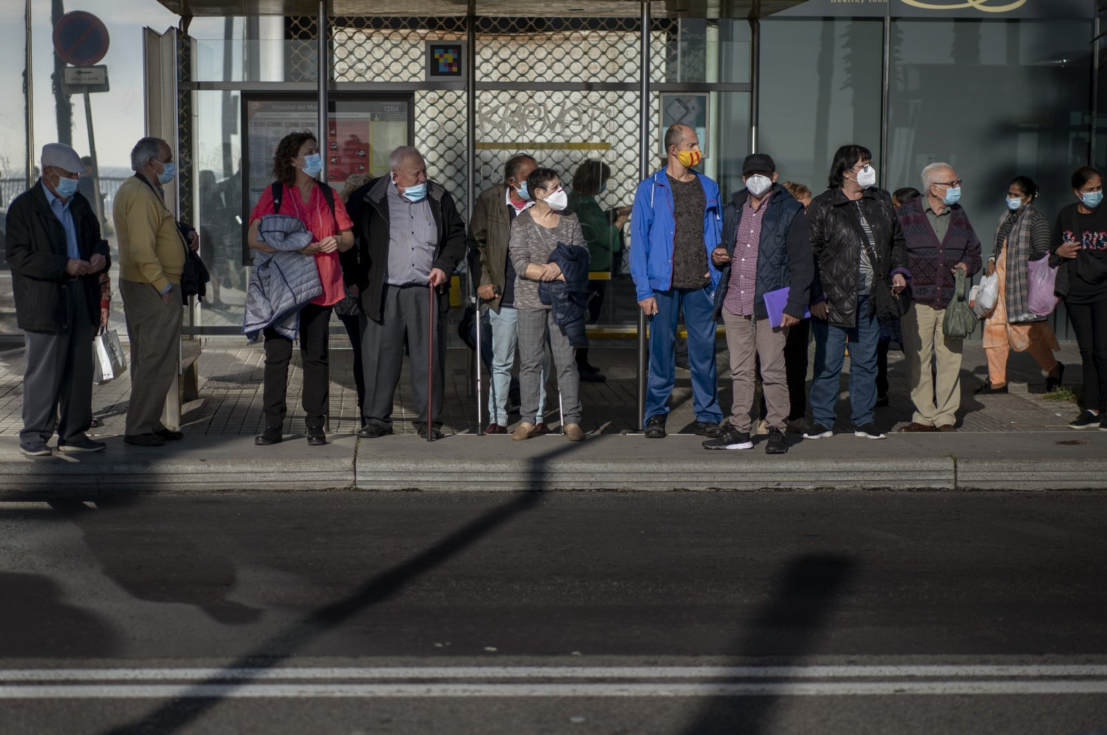 People wait for a bus in Barcelona, Spain, Oct. 23, 2020. (AP Photo)