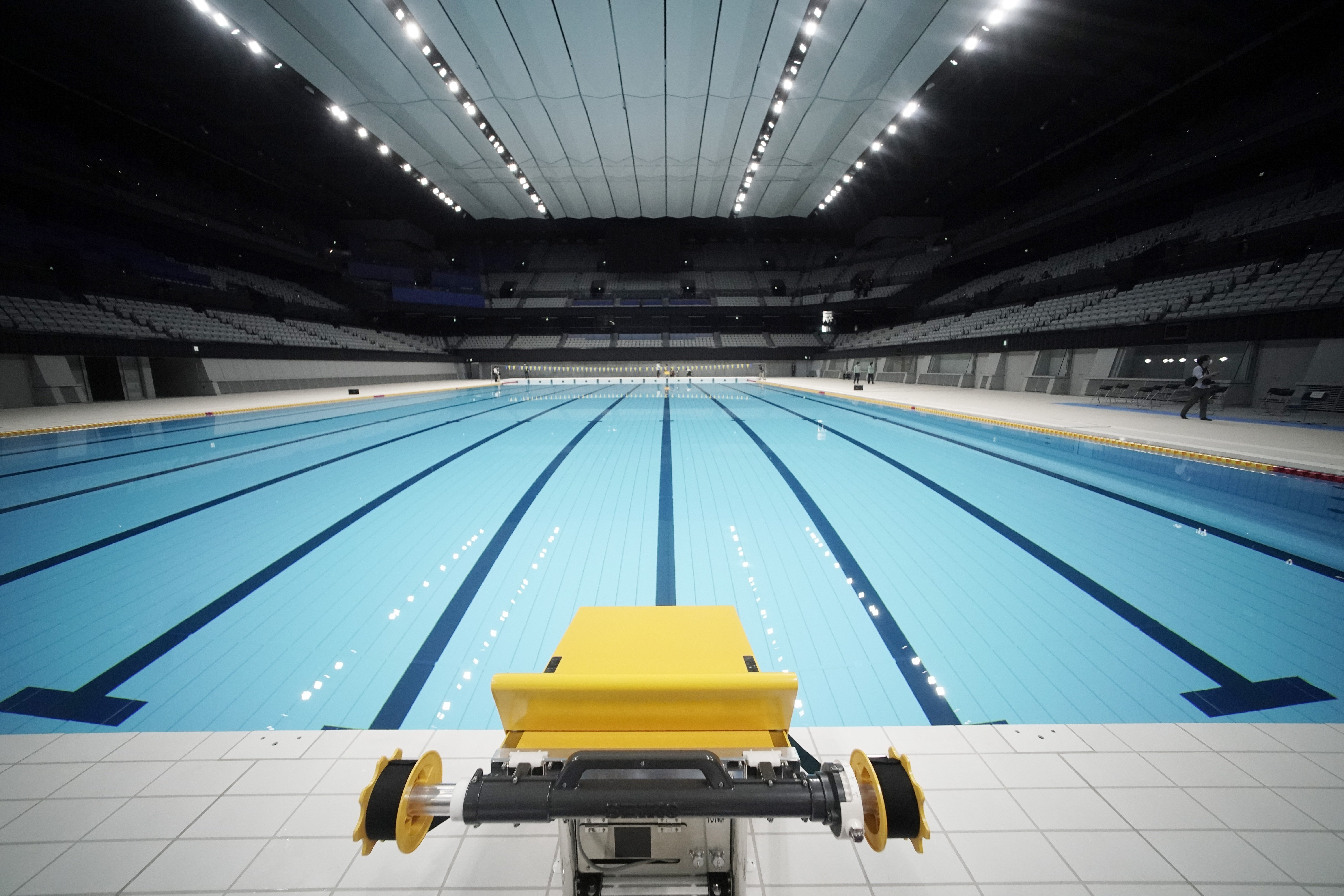 A starting block of the swimming pool at an empty Tokyo Aquatics Center following the Tokyo 2020 organizing committee's grand opening ceremony Saturday at the facility where the city plans to host Olympic artistic swimming, diving and swimming and Paralympics swimming events in 2021, Tokyo, Oct. 24, 2020. (AP Photo/Eugene Hoshiko)