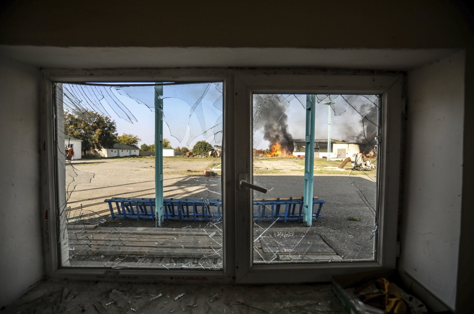 Seen through a damaged window, a fire burns at a factory following its shelling during fighting over the occupied Nagorno-Karabakh region, Tartar, Azerbaijan, Oct. 19, 2020. (AP Photo)