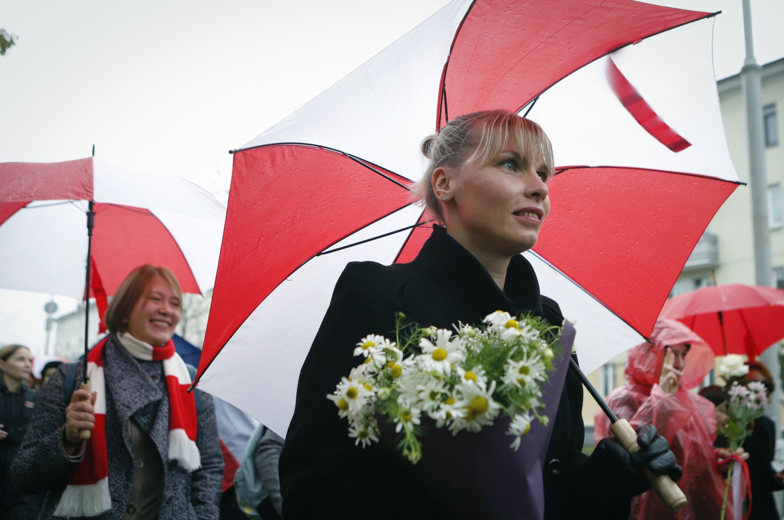Belarusian women with umbrellas in the colors of the old Belarusian national flag attend an opposition rally to protest the official presidential election results in Minsk, Belarus, Saturday, Oct. 24, 2020. (AP Photo)