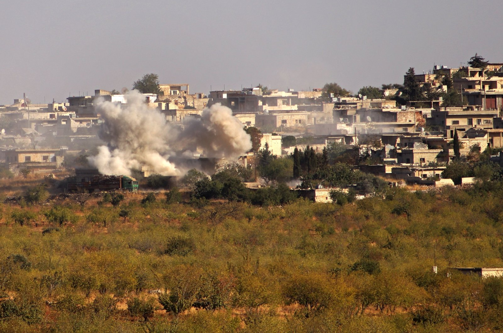 Smoke plumes rise from buildings in a village reportedly targeted with shells by Bashar Assad regime forces, Kansafra, southern Idlib province, northwestern Syria, Oct. 23, 2020. (AFP)