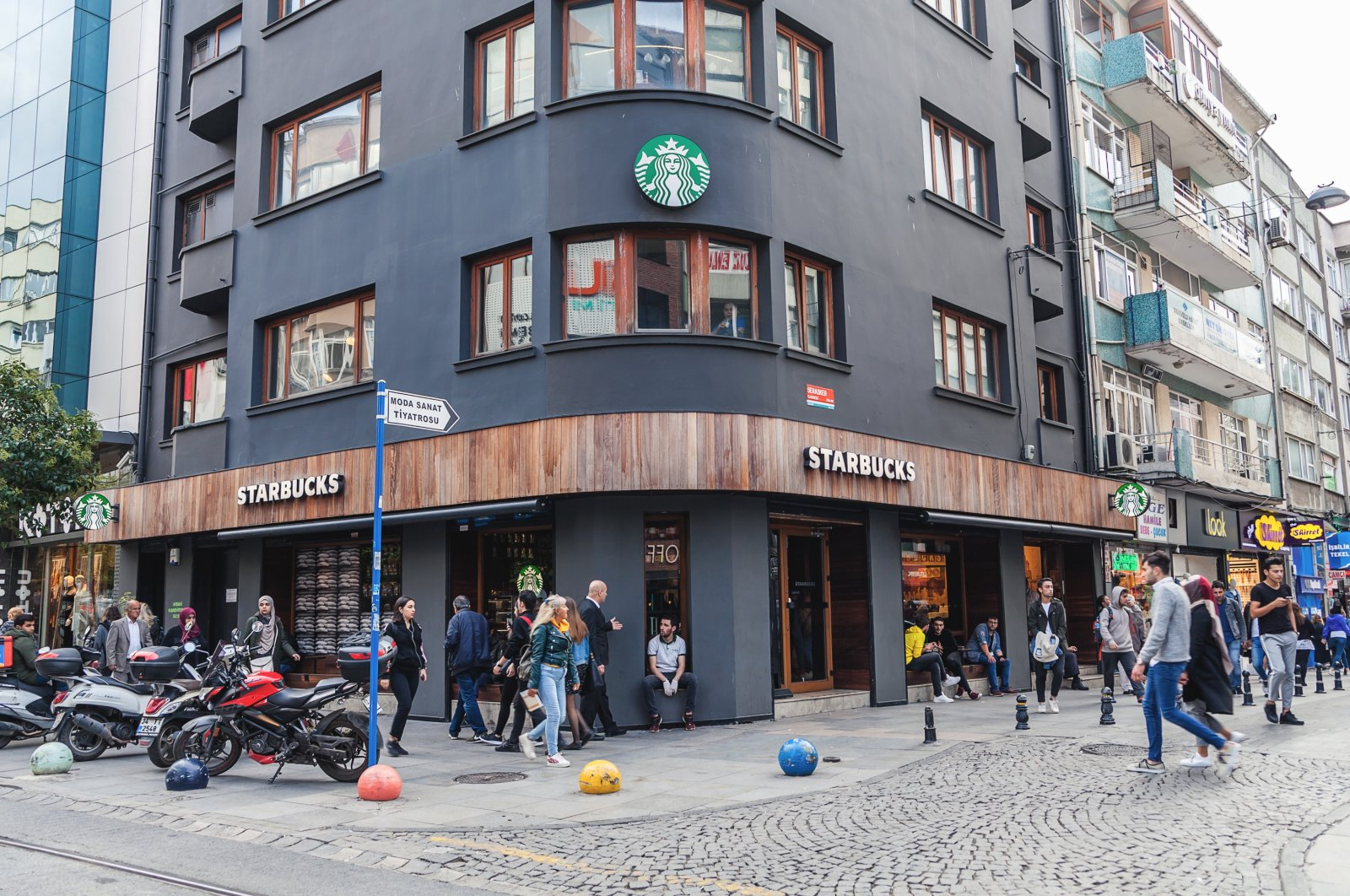 People are seen in front of a Starbucks coffee shop on the tourist street Bahariye in Kadiköy district on the Asian side of Istanbul, Oct. 4, 2018. (Shutterstock Photo)