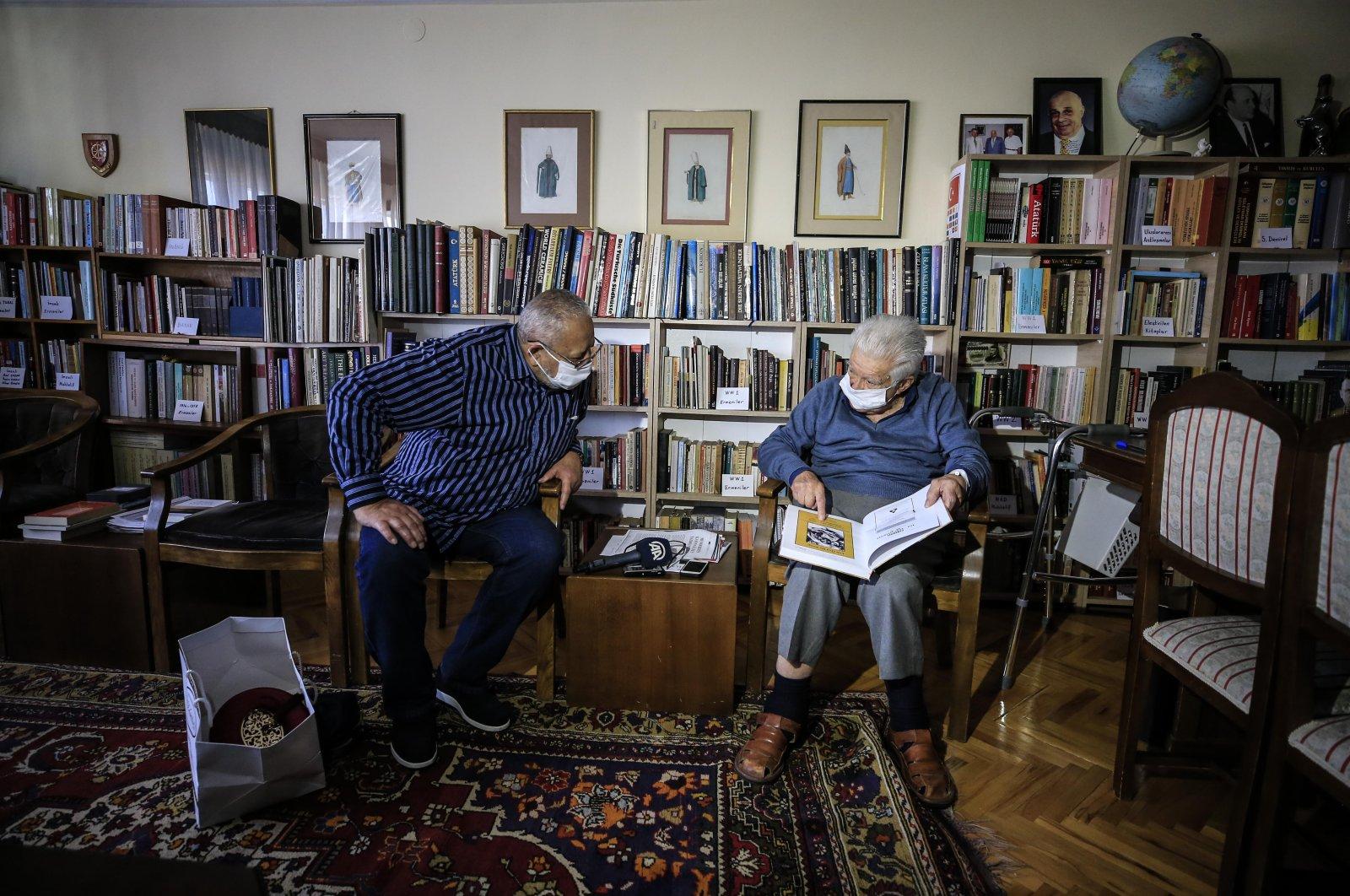 Mehmet Arif Demirer (R) shows a photo to Ahmet Kemal Atala, in the capital Ankara, Turkey, Oct. 25, 2020. (AA Photo)