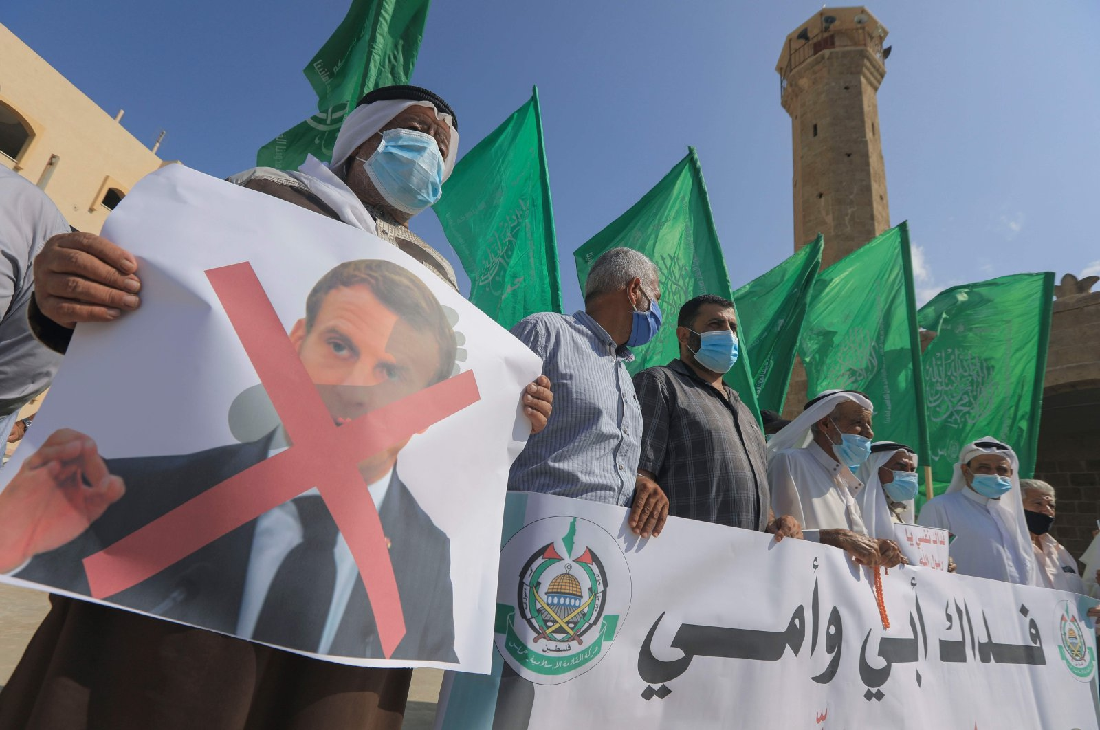 Palestinian demonstrators lift flags and placards during a rally to protest comments of French President Emmanuel Macron over Prophet Muhammed cartoons, in Deir al-Balah in the central Gaza Strip, Oct. 25, 2020. (AFP)