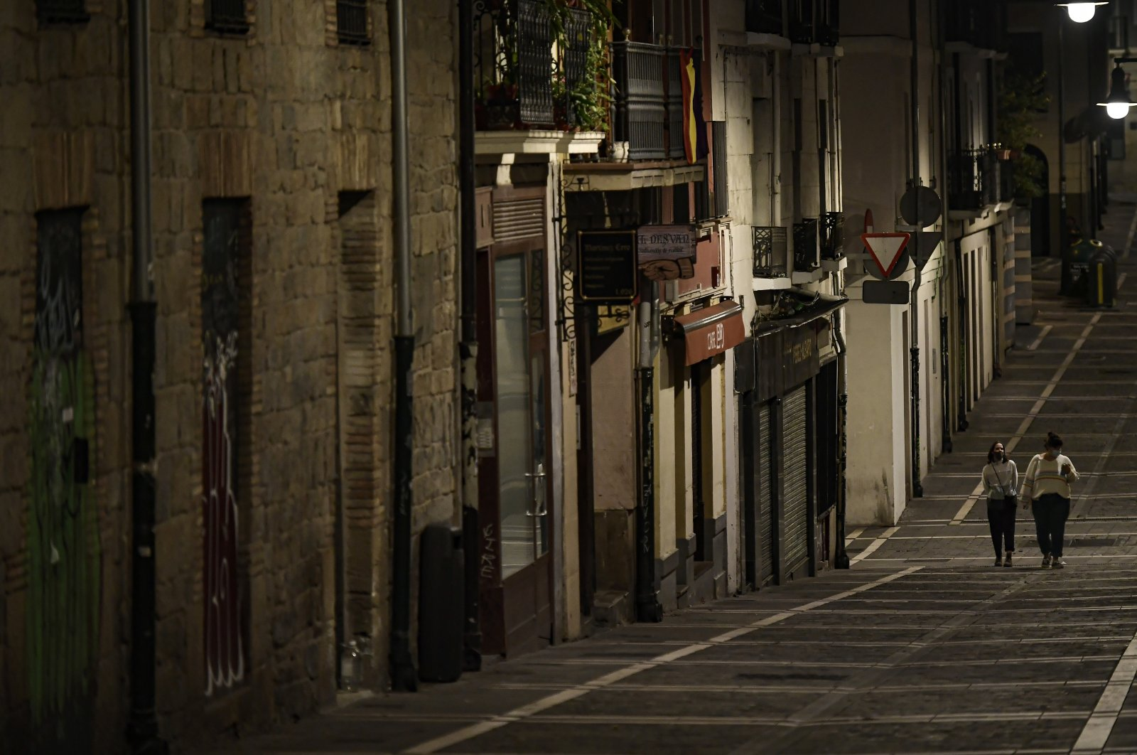 Residents wearing face mask protection as they walk along an empty Javier street, Pamplona, northern Spain, Oct. 24, 2020. (AP Photo)
