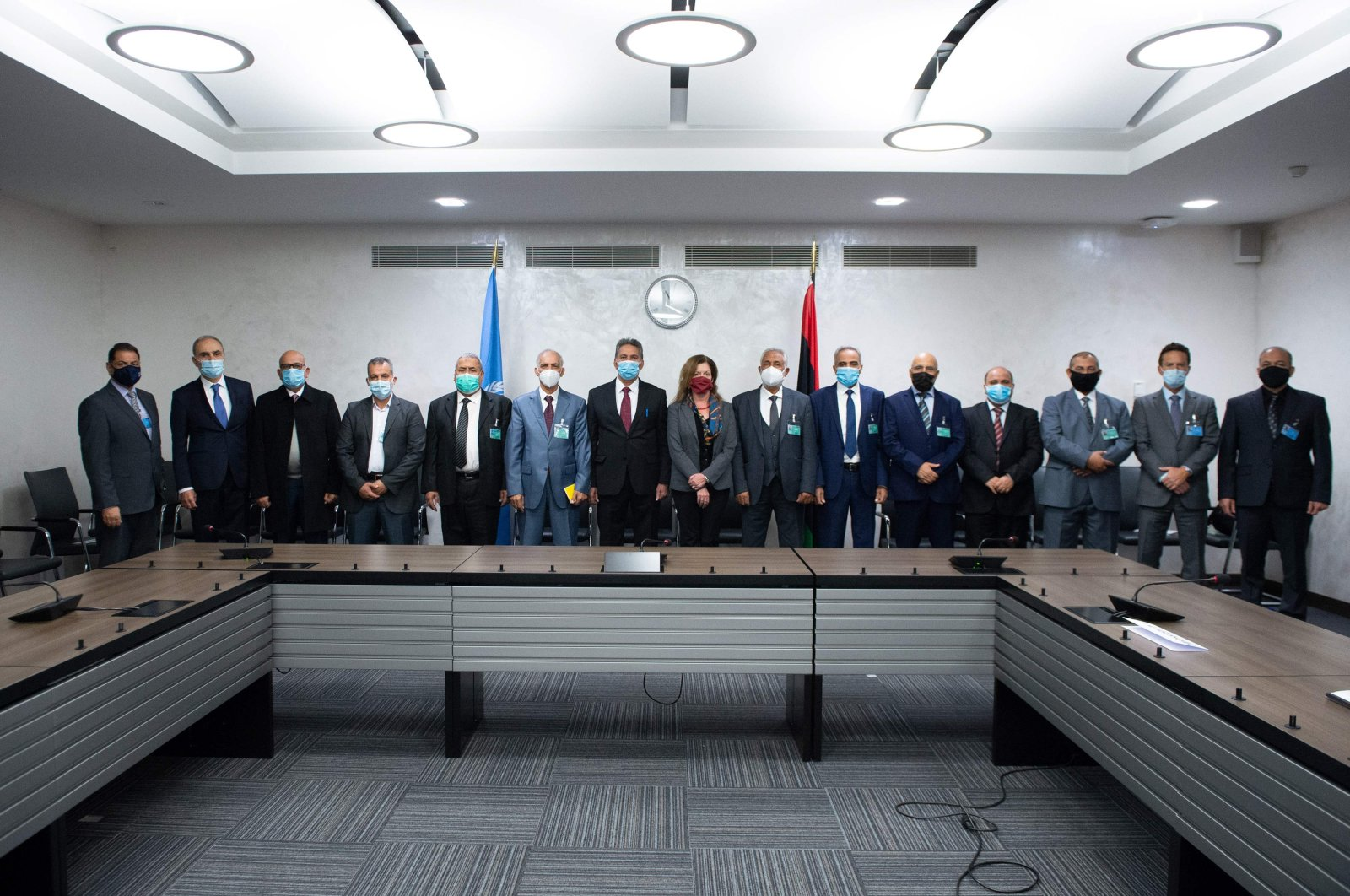 Deputy special representative of the U.N. Secretary-General for Political Affairs in Libya Stephanie Williams (8th R) and representatives of the rival factions in the Libya conflict, standing at the beginning of the talks in Geneva. (AFP File Photo)
