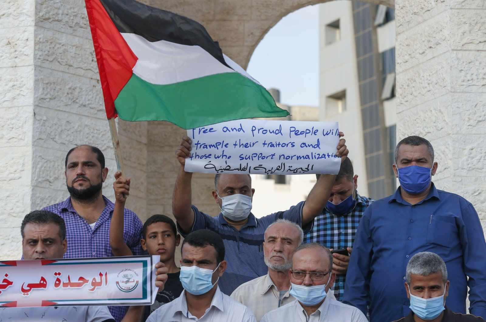 Palestinian demonstrators lift placards protesting the Sudan normalization agreement with Israel, in Rafah town in the southern Gaza Strip on Oct. 24, 2020.  (AFP Photo)