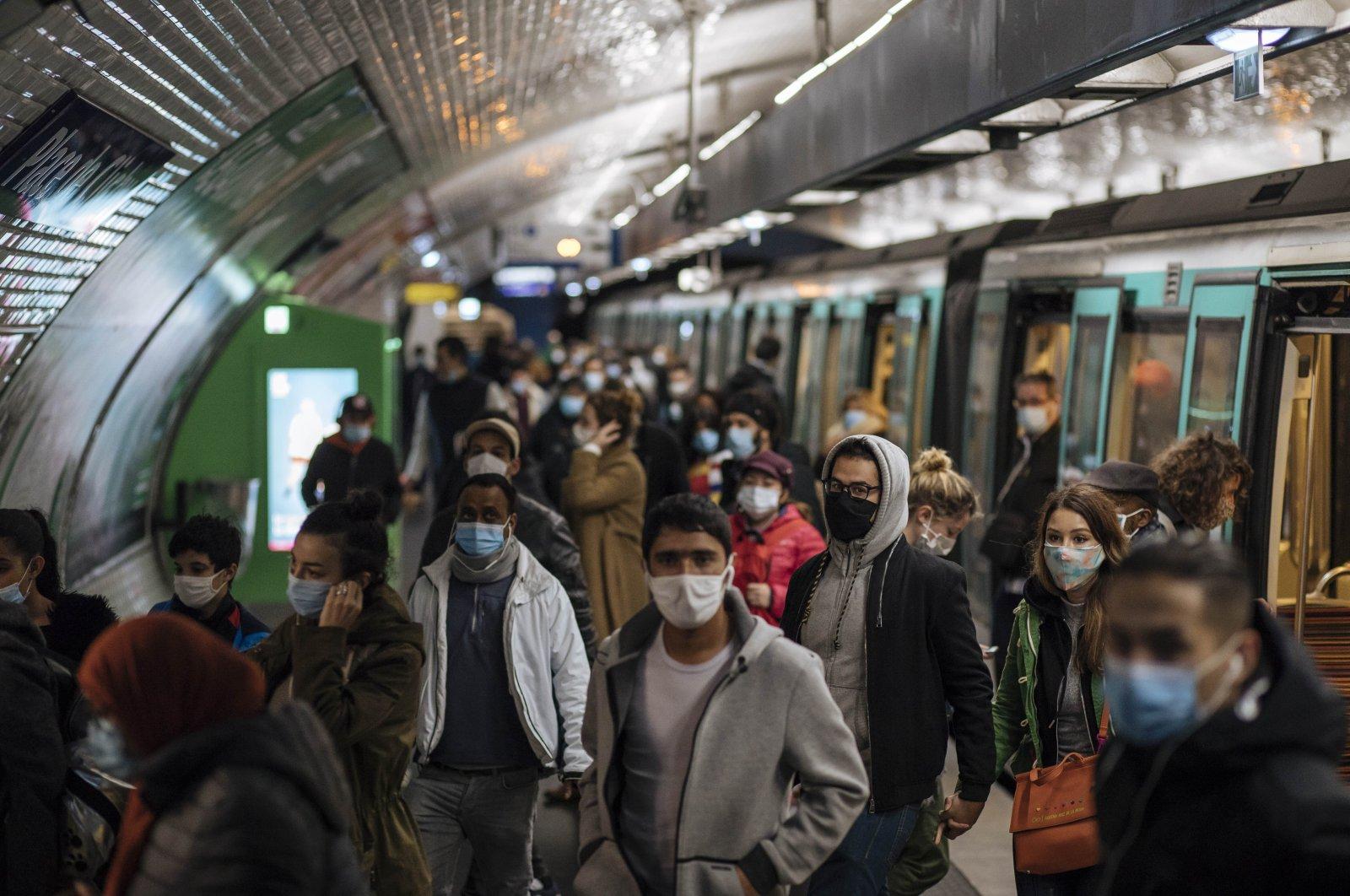 Commuters wearing face masks walk on the platform of a Paris subway, Oct. 25, 2020. (AP Photo)