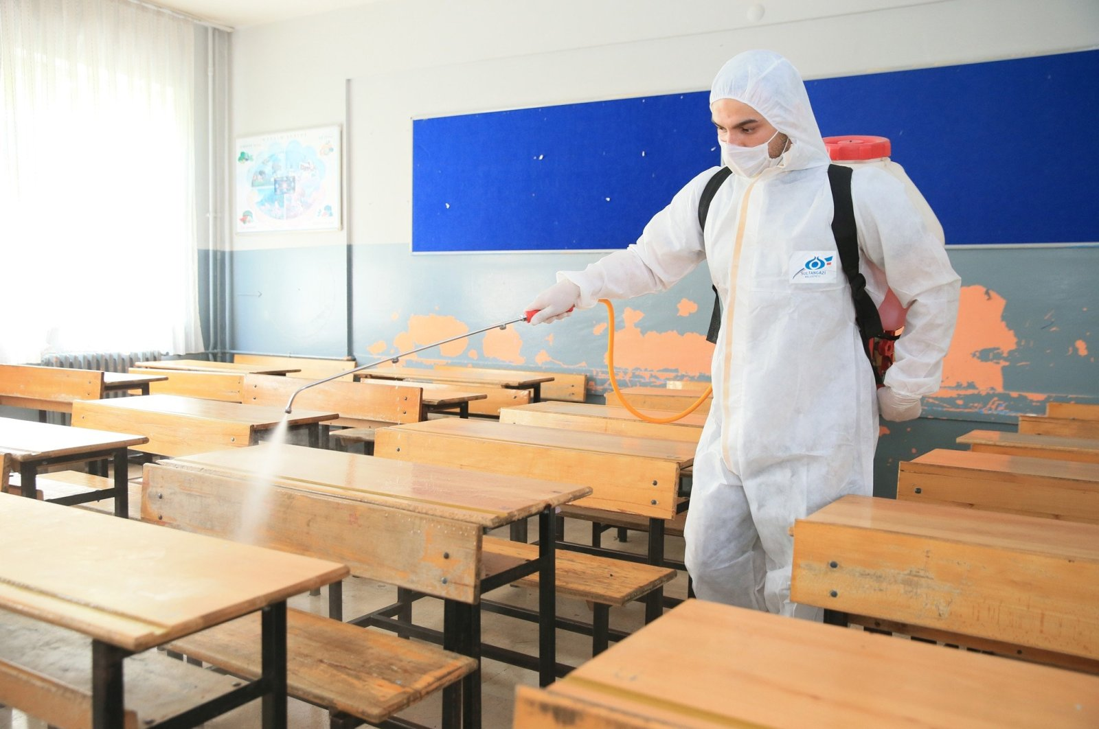 A worker from the Sultangazi Municipality sanitizes a classroom in Istanbul on June 19, 2020. (IHA Photo)