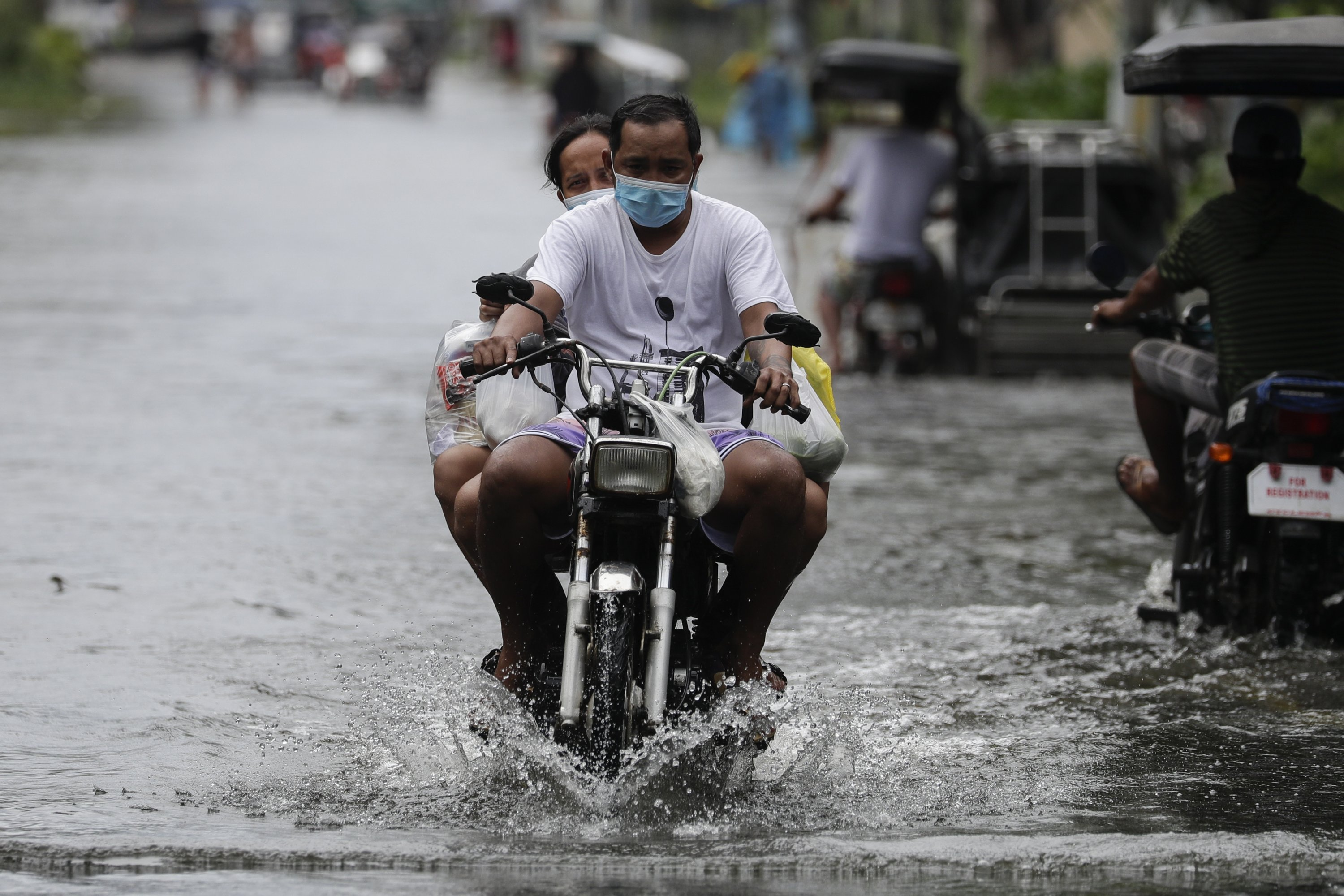 Residents on a motorcycle negotiate a flooded road due to Typhoon Molave in Pampanga province, northern Philippines, Monday, Oct. 26, 2020. (AP Photo)