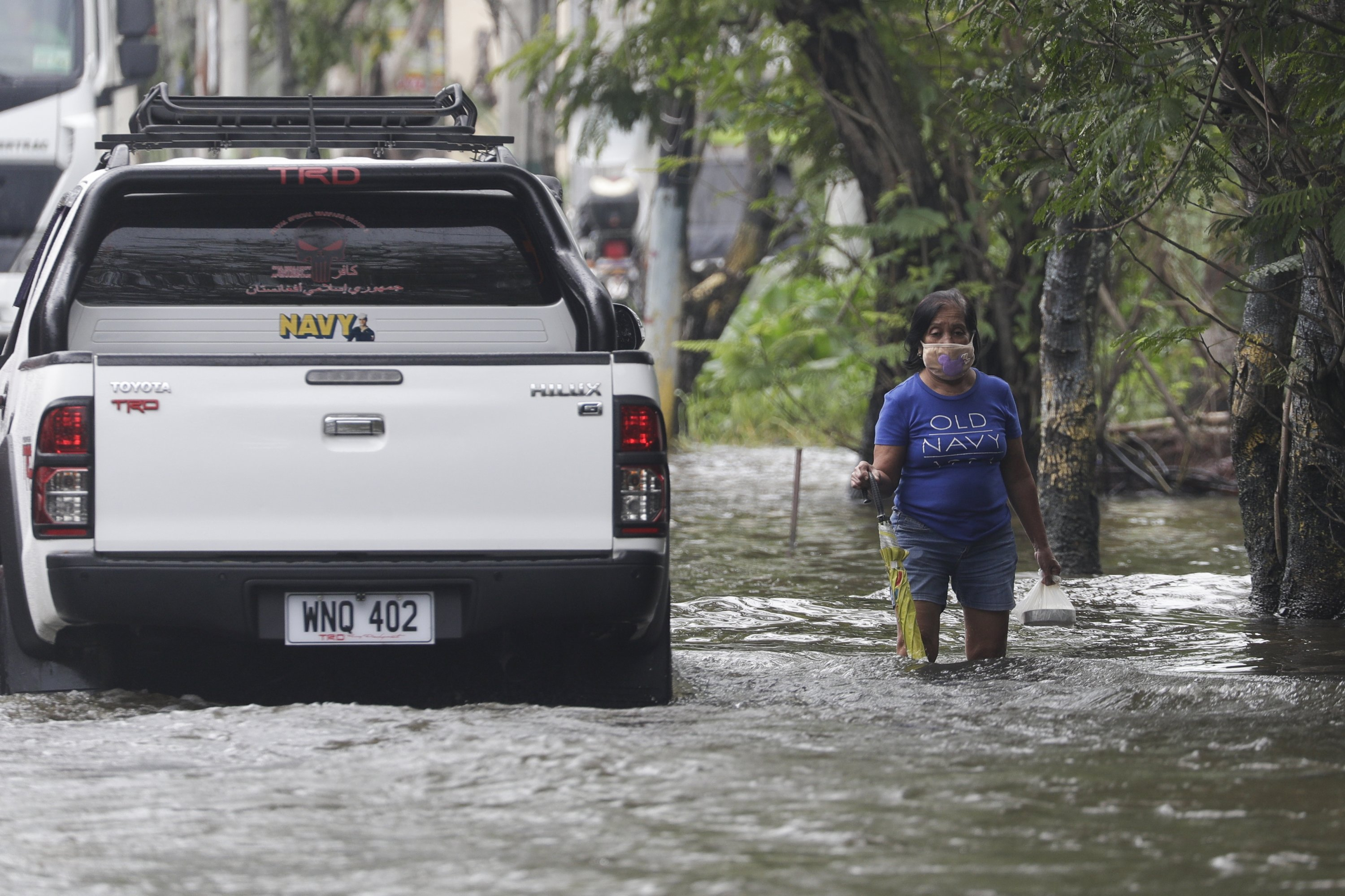 A resident negotiates a flooded road due to Typhoon Molave in Pampanga province, northern Philippines on Monday, Oct. 26, 2020. (AP Photo)