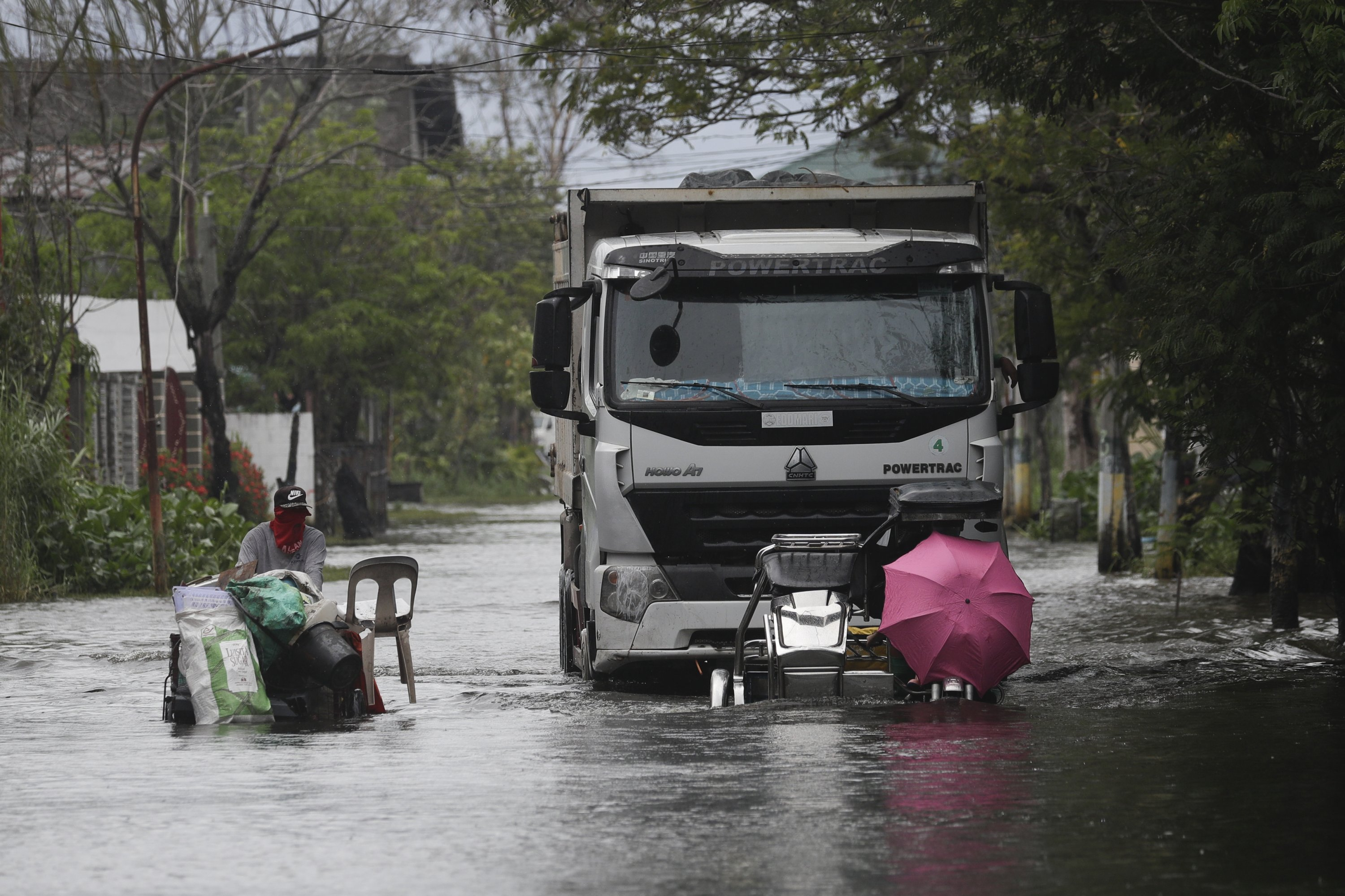 Motorists with an umbrella negotiate a flooded road due to Tyophoon Molave in Pampanga province, northern Philippines, Monday, Oct. 26, 2020. (AP Photo)