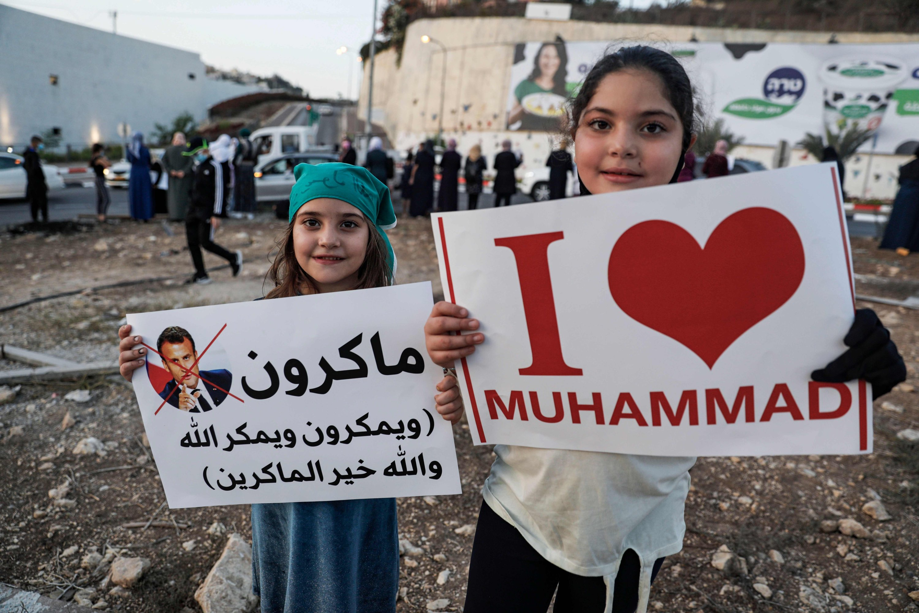 Young Arab Israeli Muslim girls hold up signs during a rally protesting against the comments of French President Emmanuel Macron over Prophet Mohammed cartoons, in the Arab town of Umm-Al Fahem in Northern Israel on Oct. 25, 2020. (AFP)