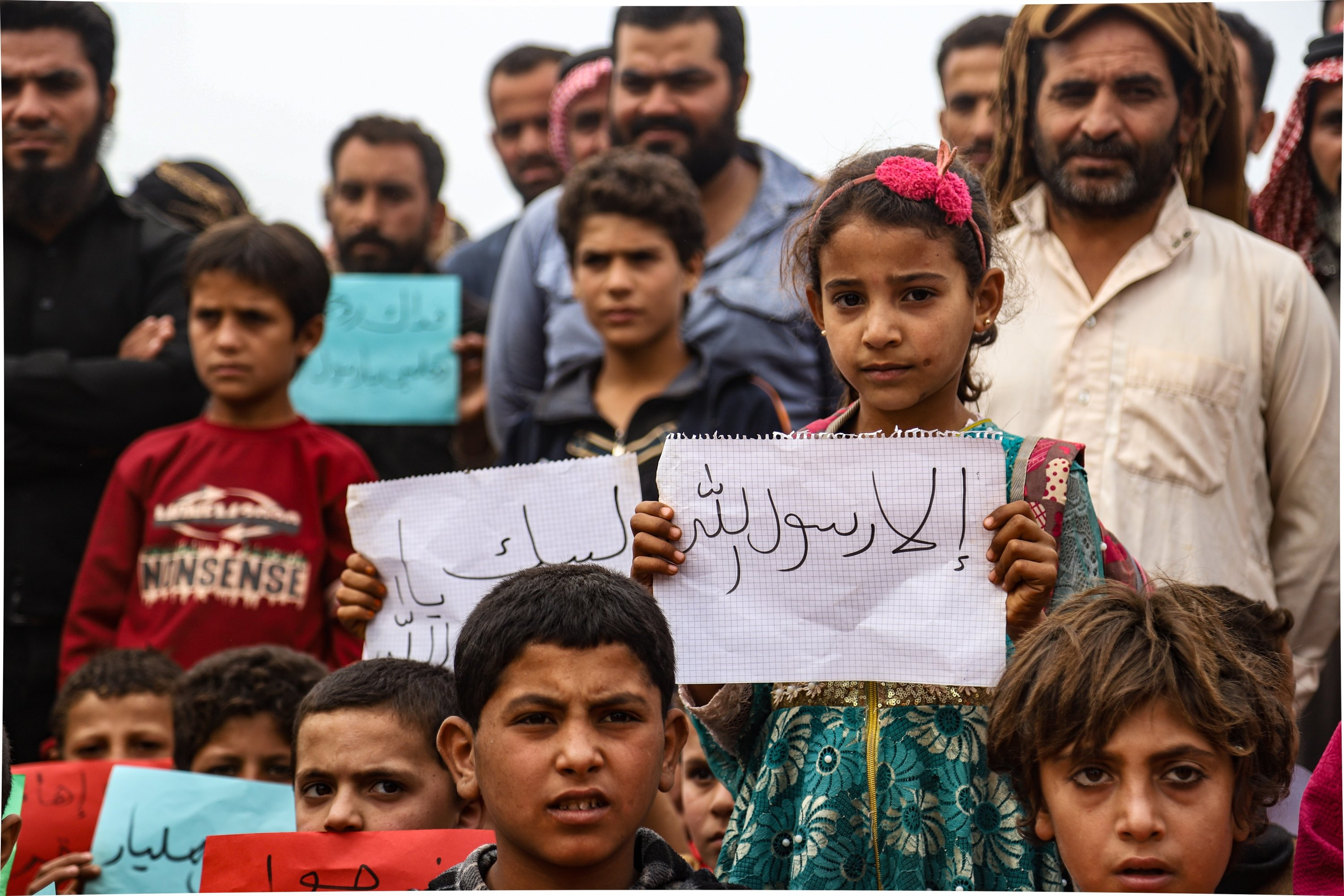 Syrians in Idlib protest Macron's remars with banners writing