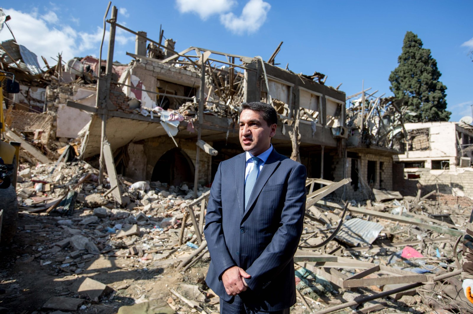 Azerbaijani Presidential aide Hikmet Hajiyev stands in front of a building destroyed in Armenian shelling in the city of Ganja, Azerbaijan on Oct. 13, 2020. (Sabah Photo)